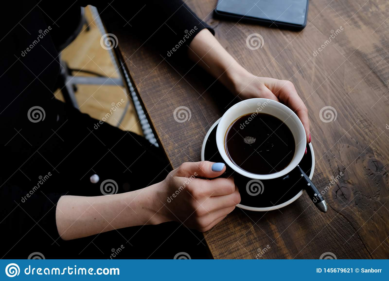 The girl holds a Cup of coffee on a wooden table in the cafe. Near the phone. Coffee-break. The concept of food, business,
