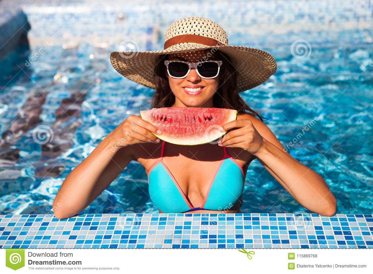 A girl holds half a red watermelon over a blue pool, relaxing o