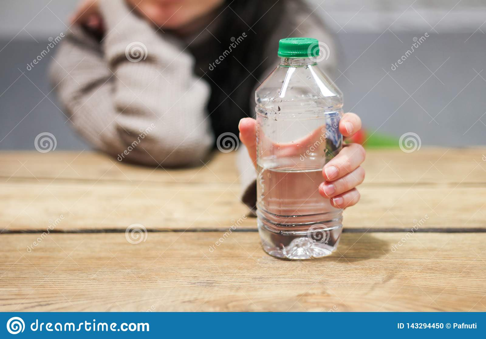 Girl holds in her hand a bottle of water on the table.