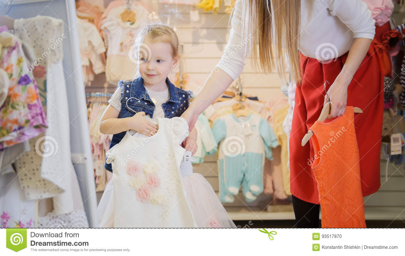 23aa4202dd A blonde little girl is holding hangers with new summer clothes in front of  a mirror in a children`s clothing store