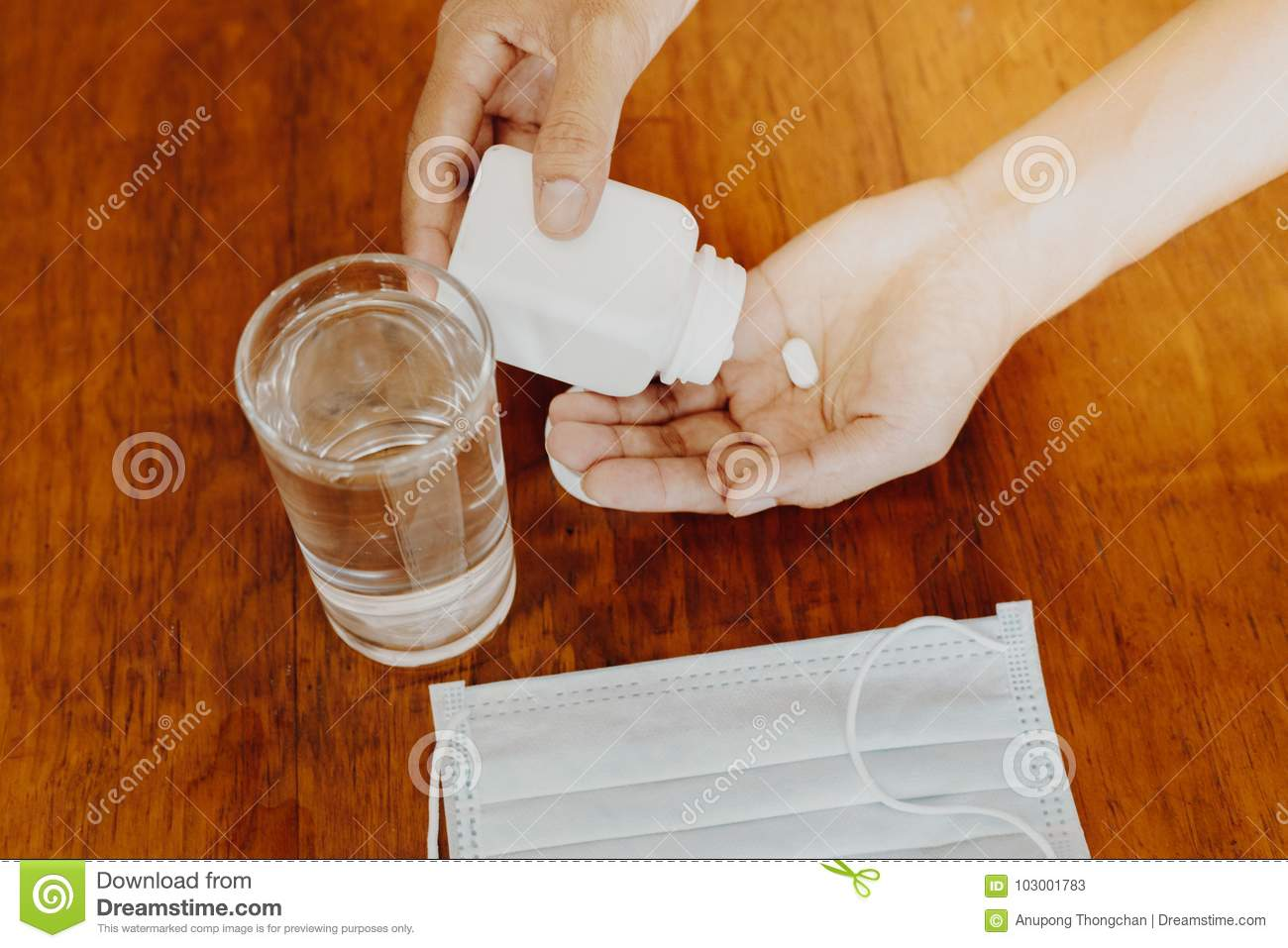 He girl holds the medicine in her hand with a glass of water Protective mask on a wooden table