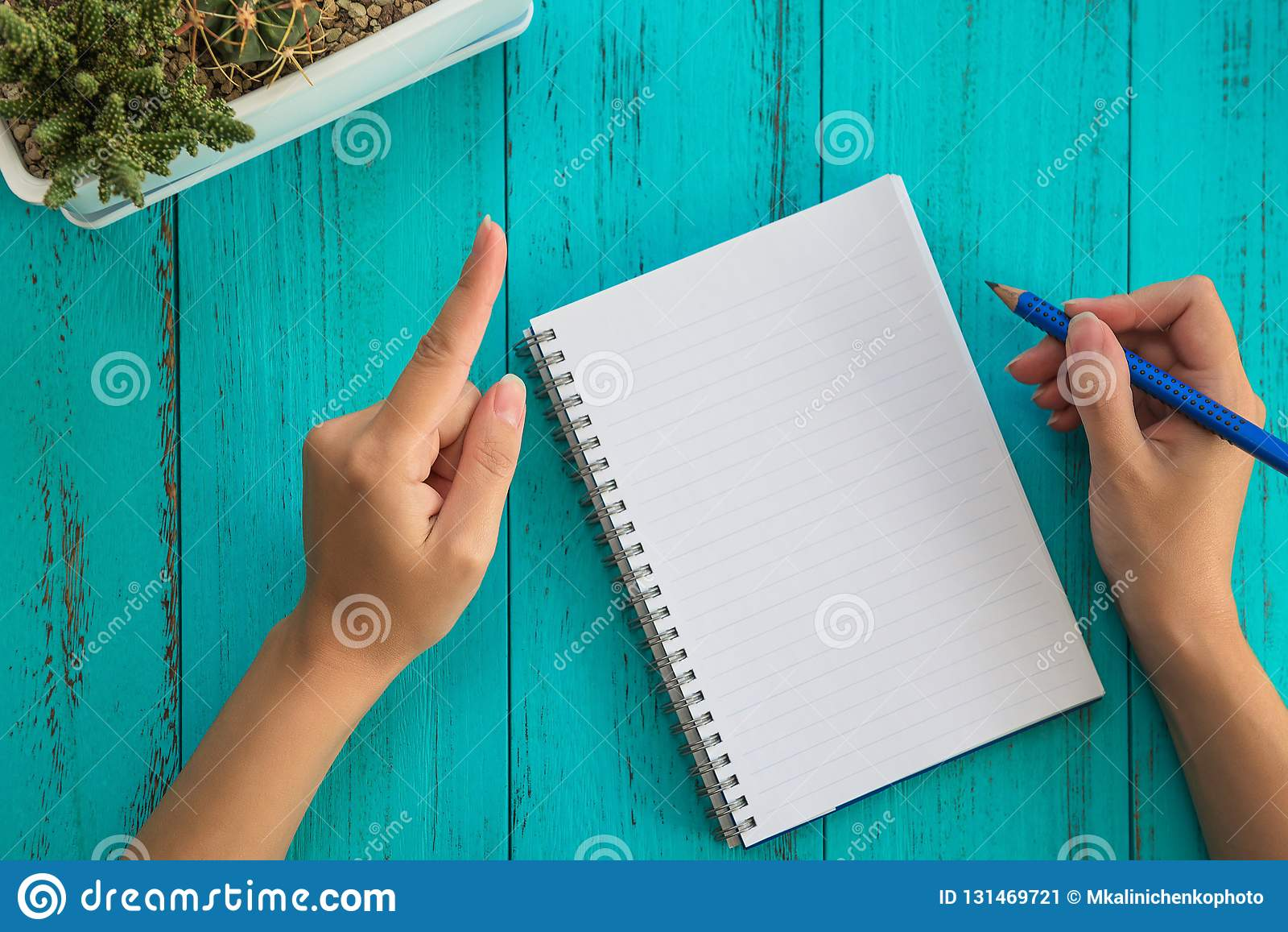 Girl holds pencil, prepares to write down goals for future in notebook, blue wooden table. Education and goals concept background
