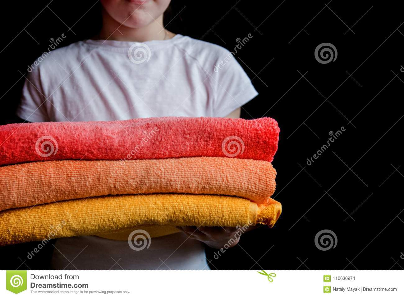 A girl holds towels in their hands