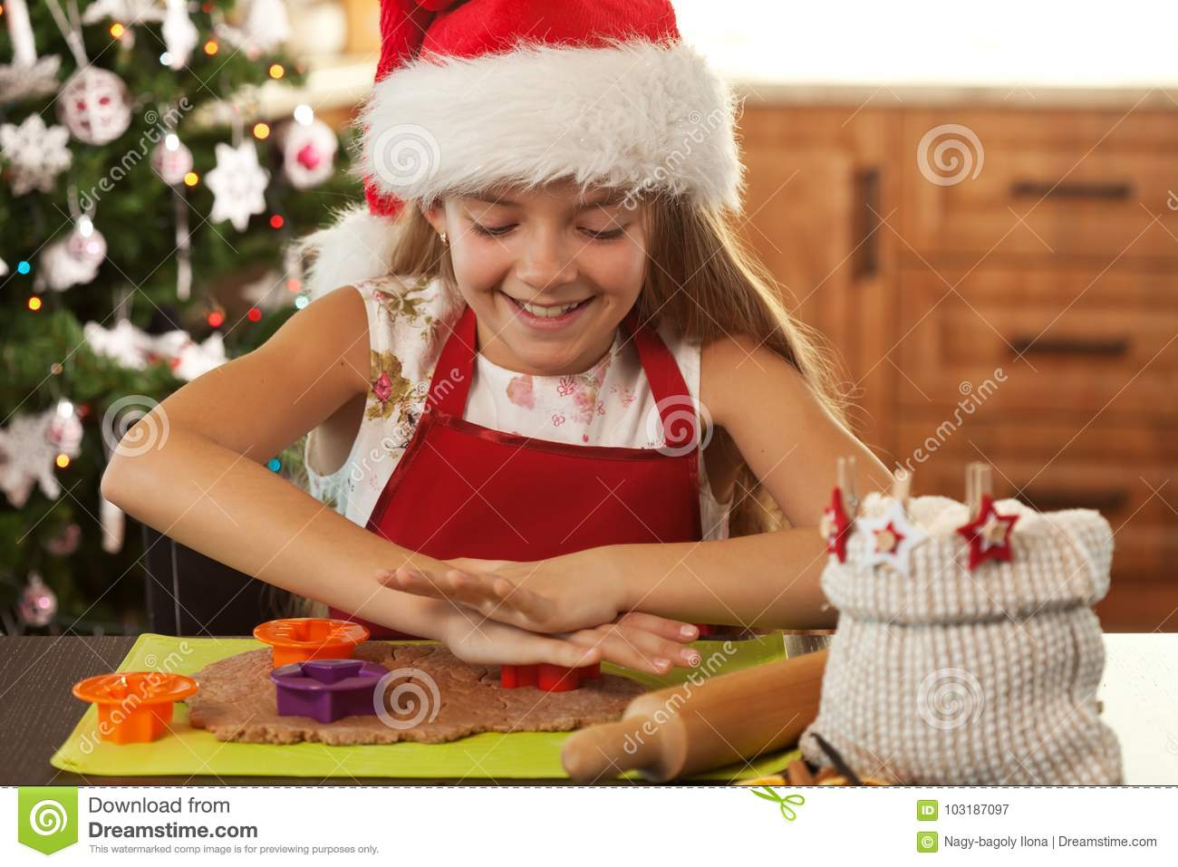 Girl in holidays mood making gingerbread cookies - cutting dough