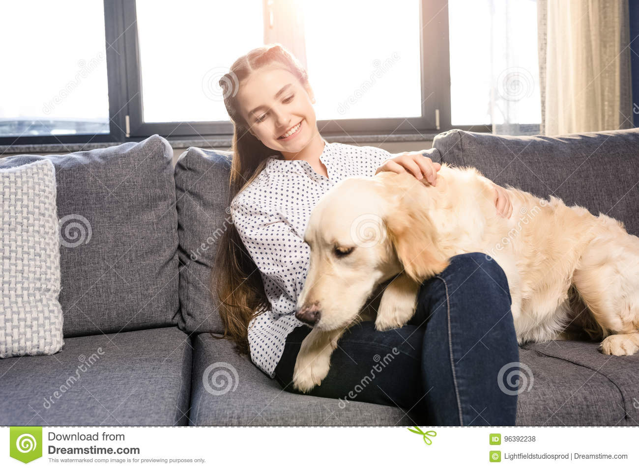 Girl Hugging Golden Retriever Dog On Sofa At Home Stock Photo