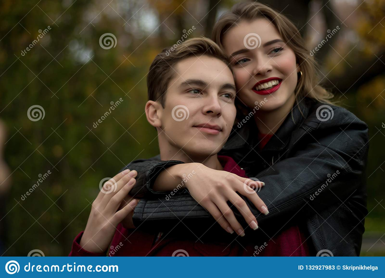 Girl Hugs A Guy And Smiles, Autumn. Hug From Behind