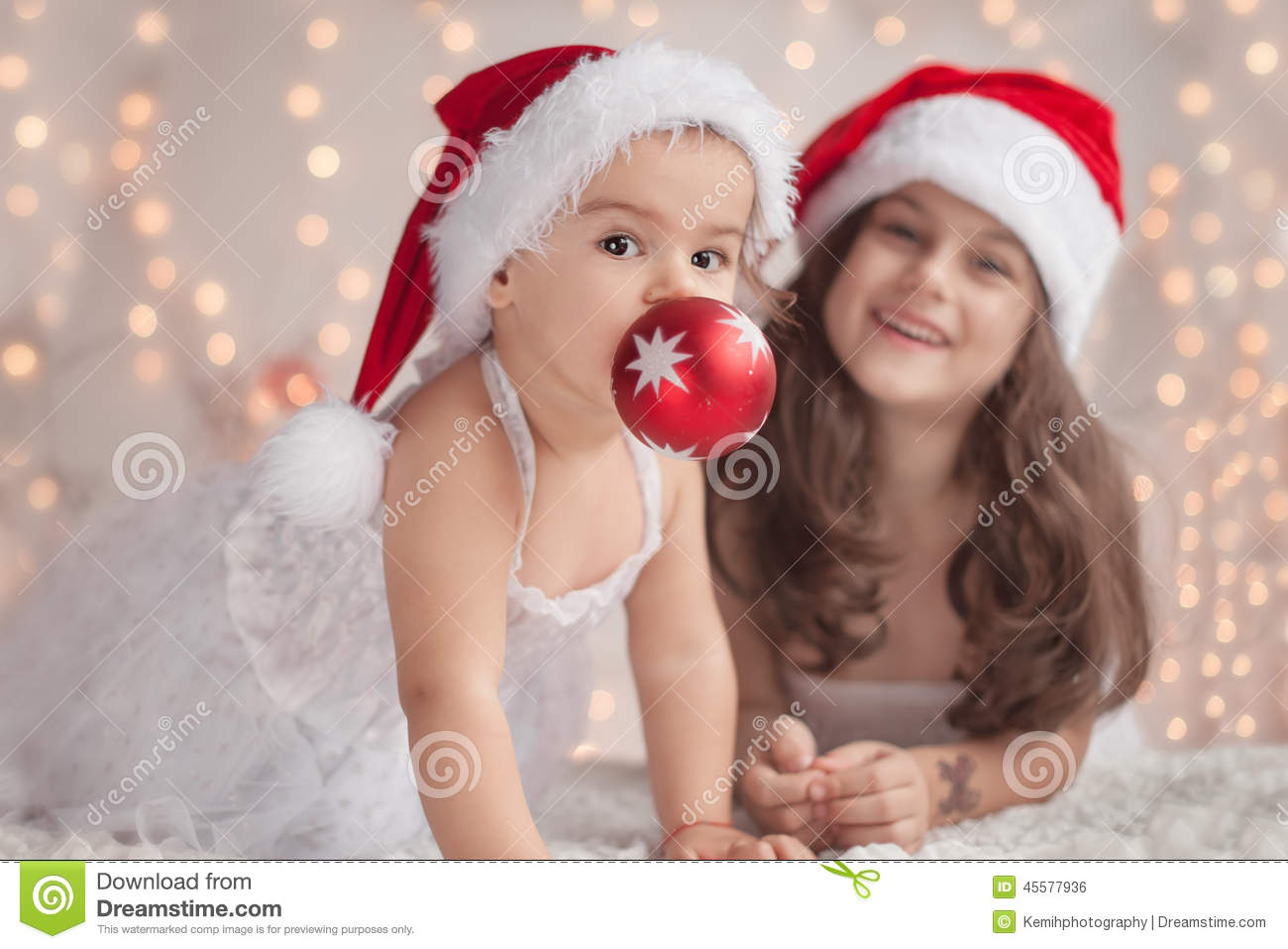 Girl hugs her little sister both wearing red christmas caps and stock