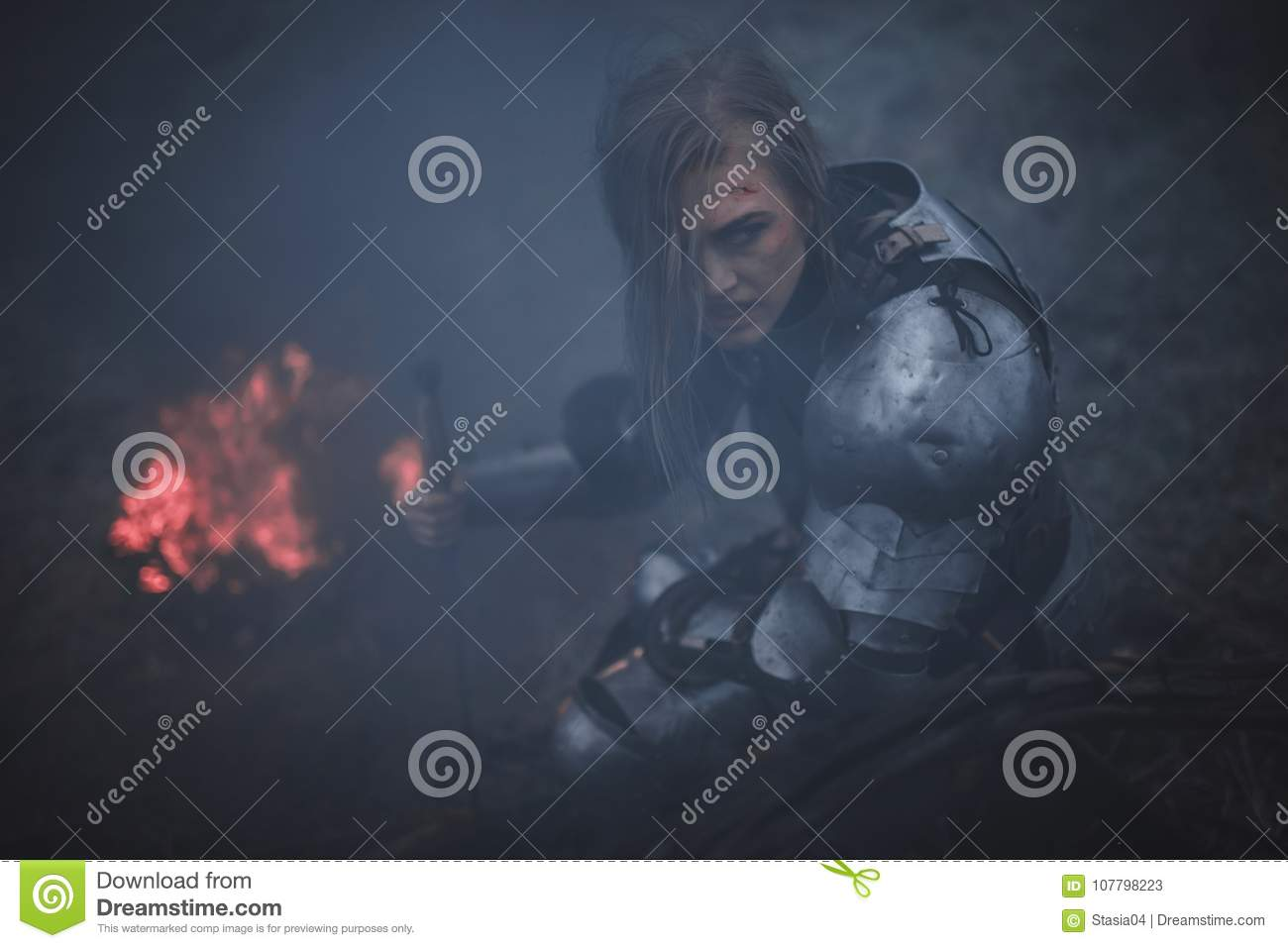 Girl in image of Jeanne d`Arc in armor and with sword in her hands kneels against background of fire and smoke.