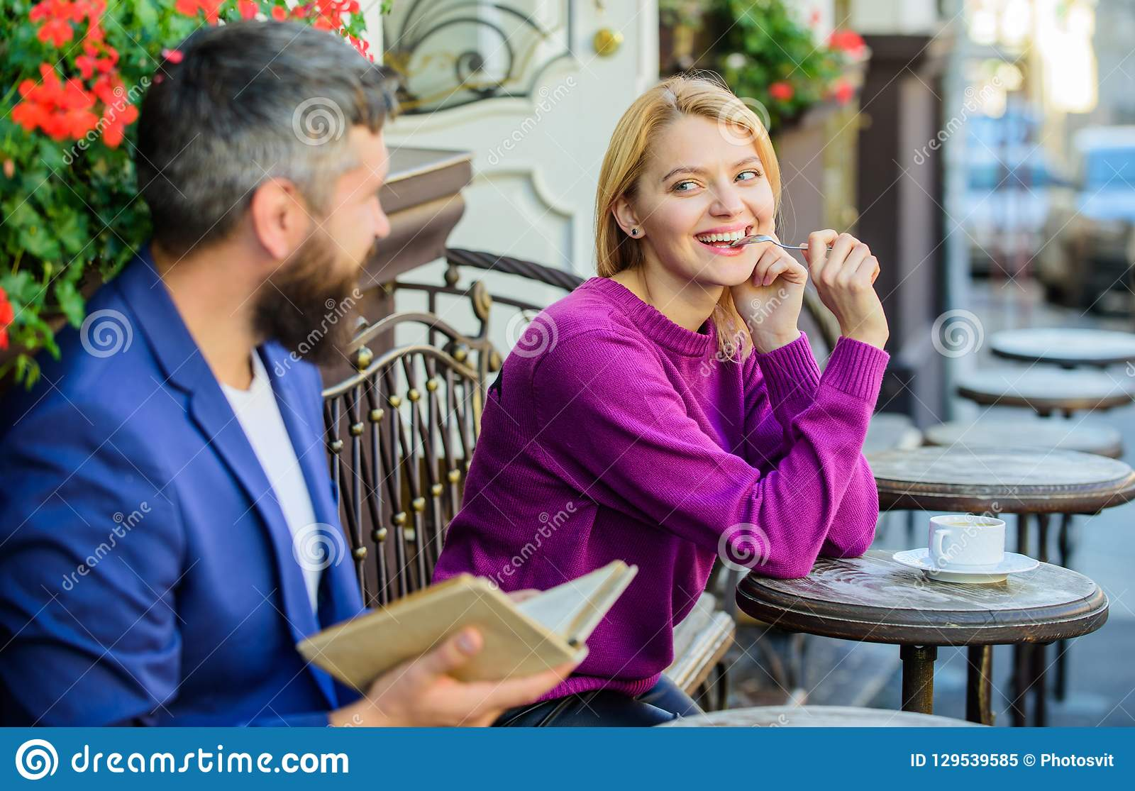 Girl interested what he read. Meeting people with similar interests. Man and woman sit cafe terrace. Literature common