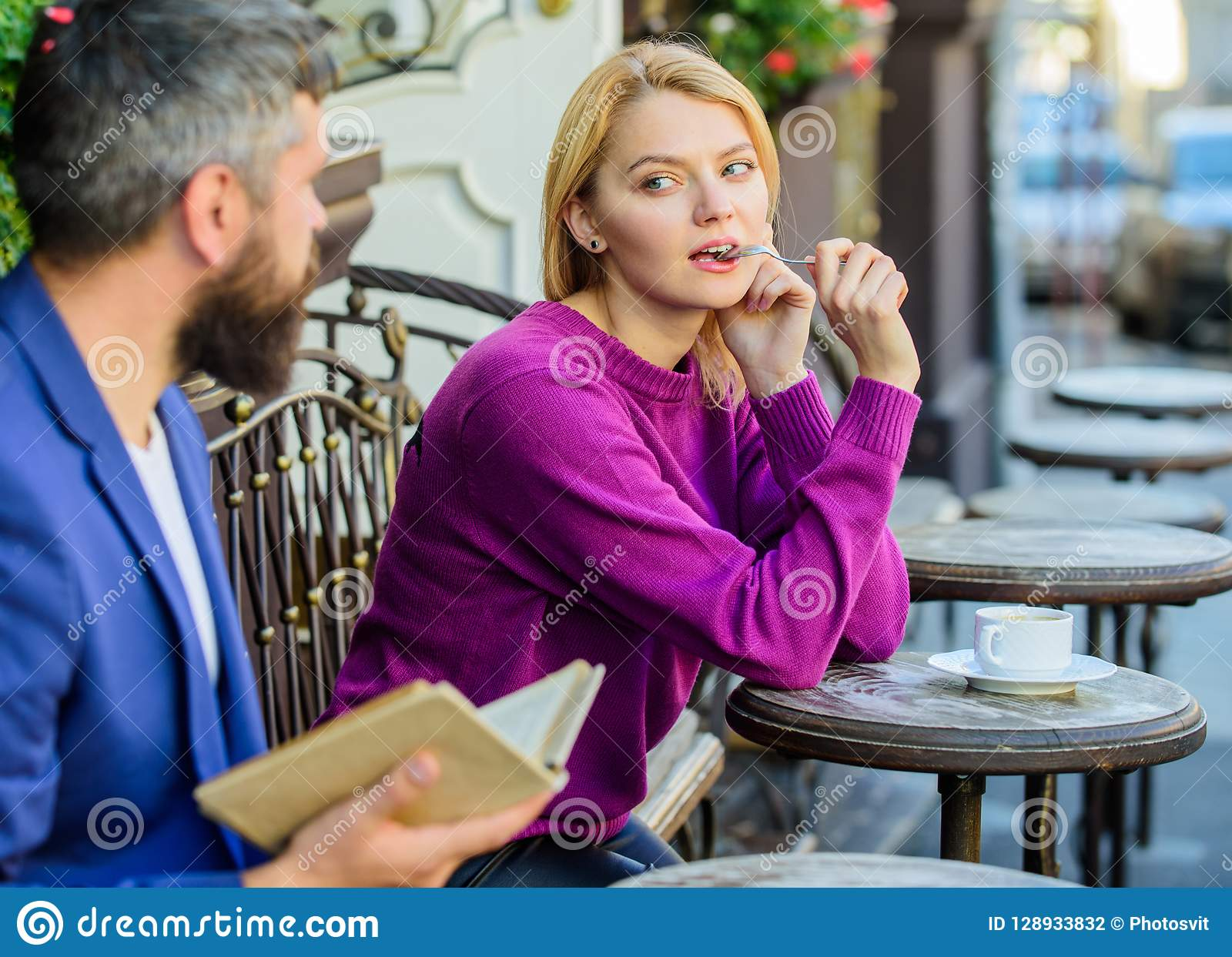 Girl interested what he reading. Guide to dating. Meeting people with similar interests. Man and woman sit cafe terrace
