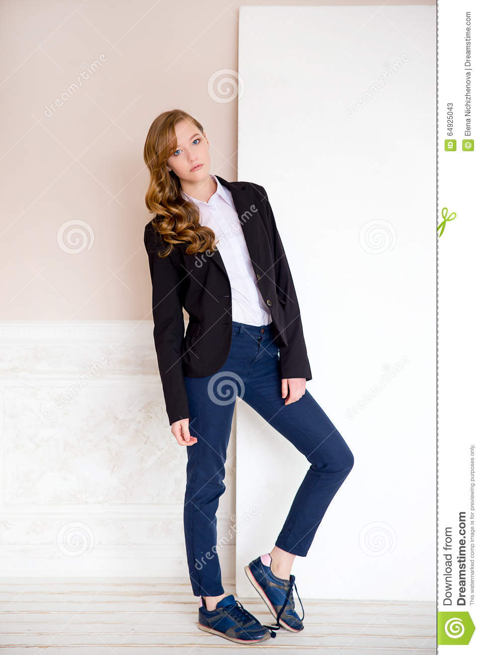 The girl in a jacket on a beige background stock image Black shirt blue jeans