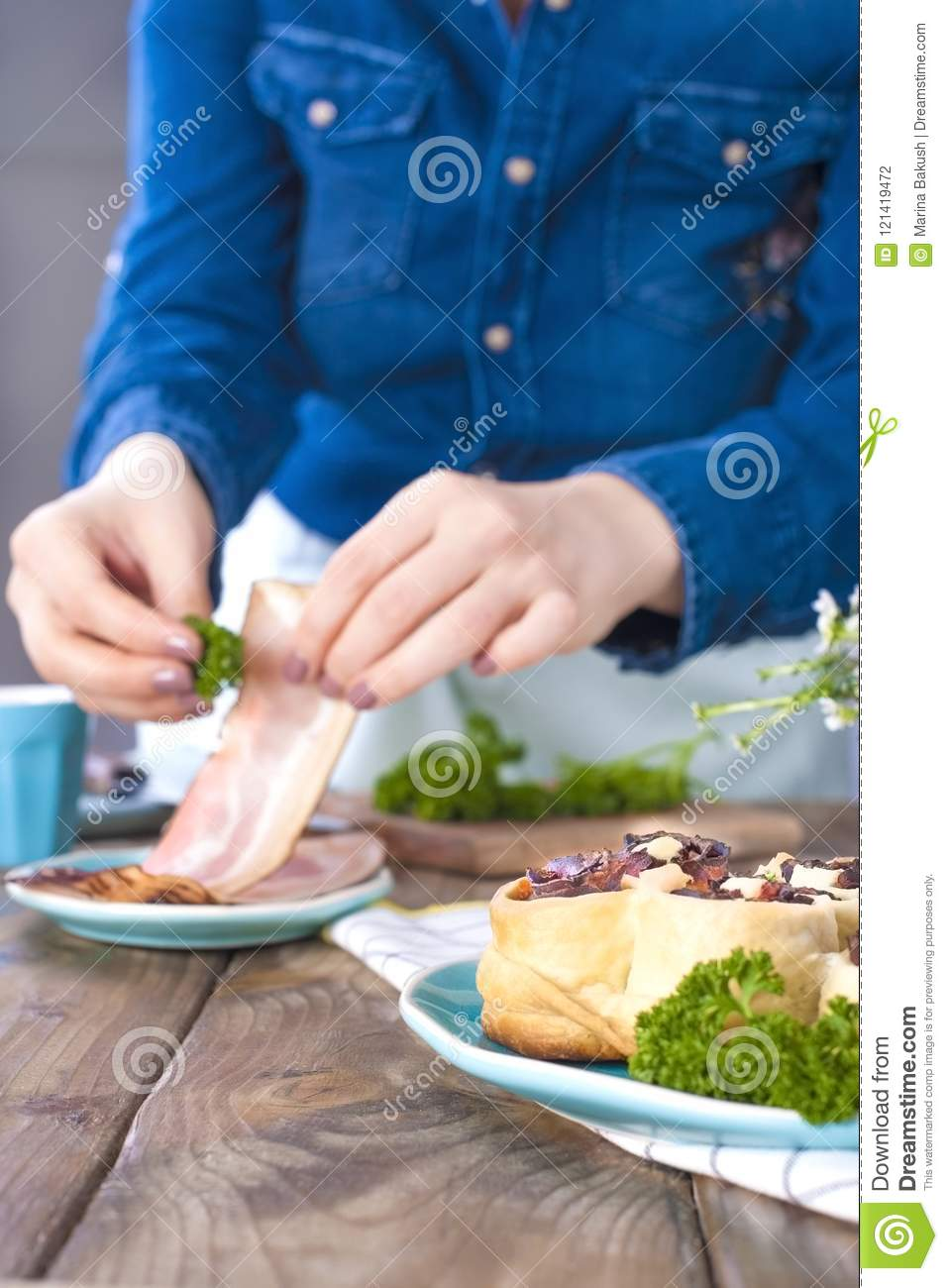 A girl in jeans clothes prepares a lunch of bacon and dough, with fresh herbs. Brown wooden background. Kramic dishes of blue cet.