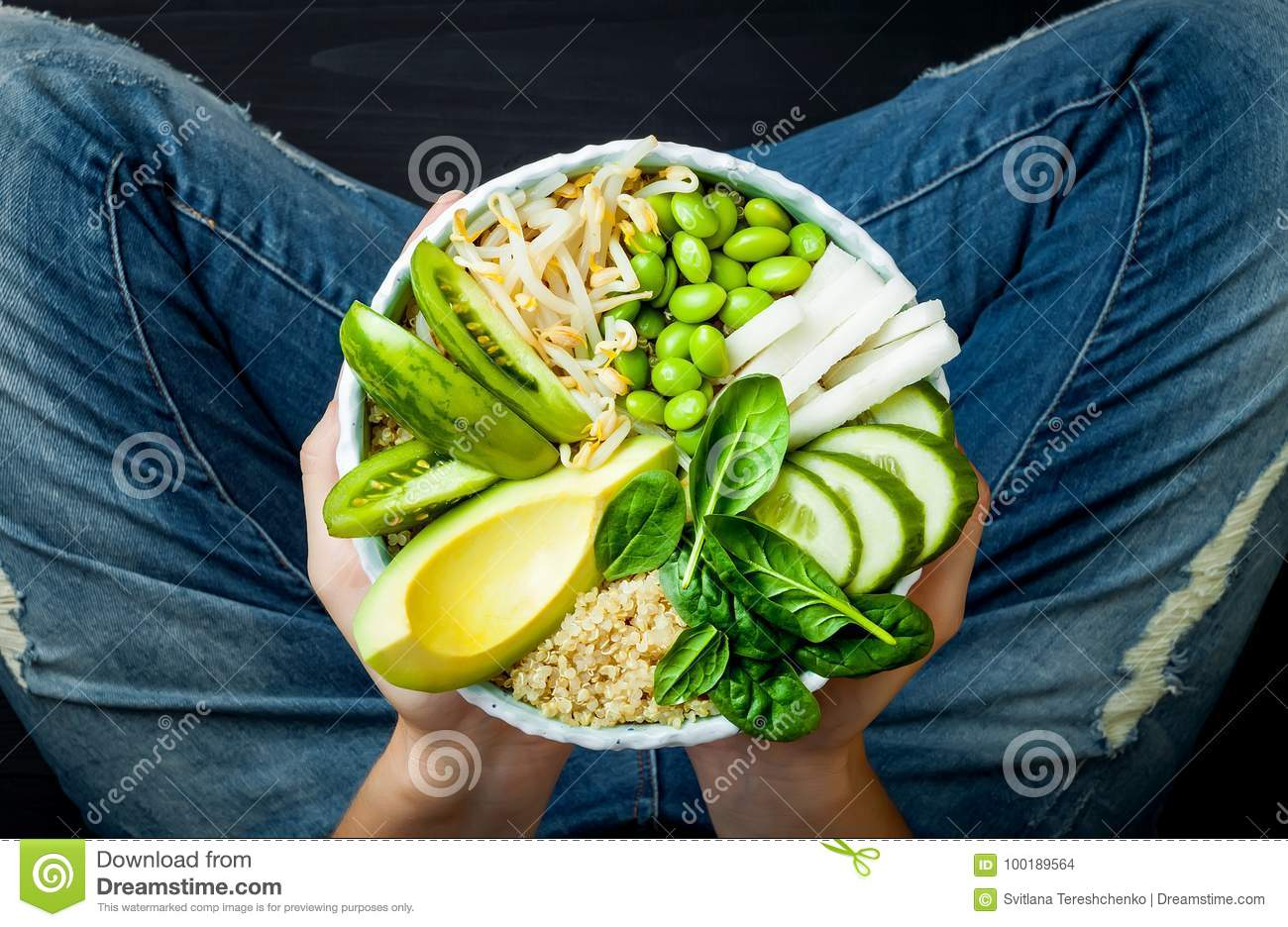 Girl in jeans holding vegan, detox green Buddha bowl with quinoa, avocado, cucumber, spinach, tomatoes, mung bean sprouts, edamame