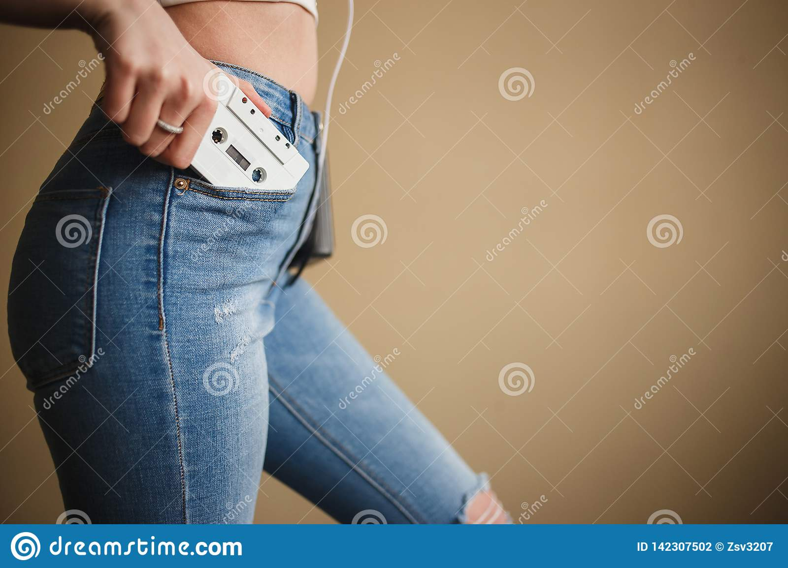 Girl in Jeans with White Audio Cassette. Close up. Concept of Hipsters, Love Retro Music, Dance Party 90s