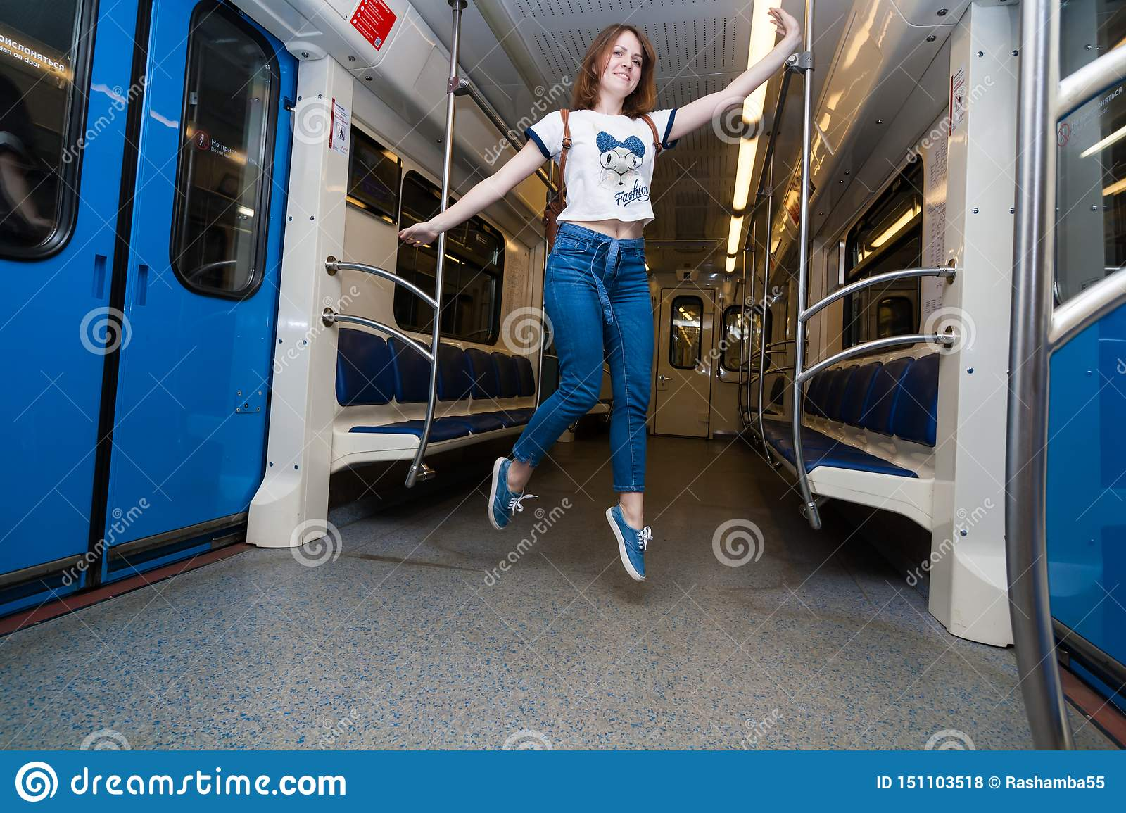 Girl jump in empty subway train. She is in blue jeans and white t-short