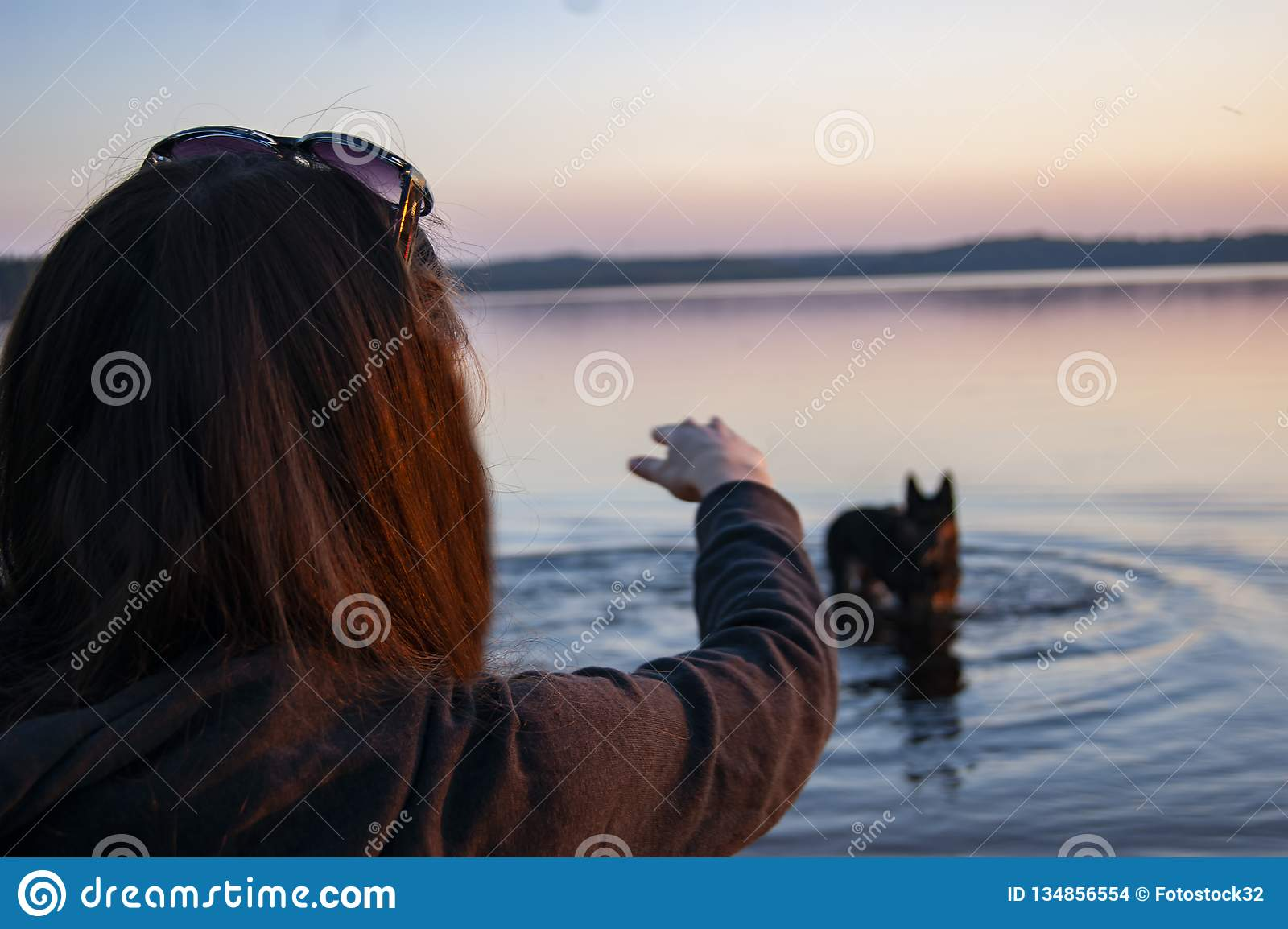 The girl on the lake playing with a dog