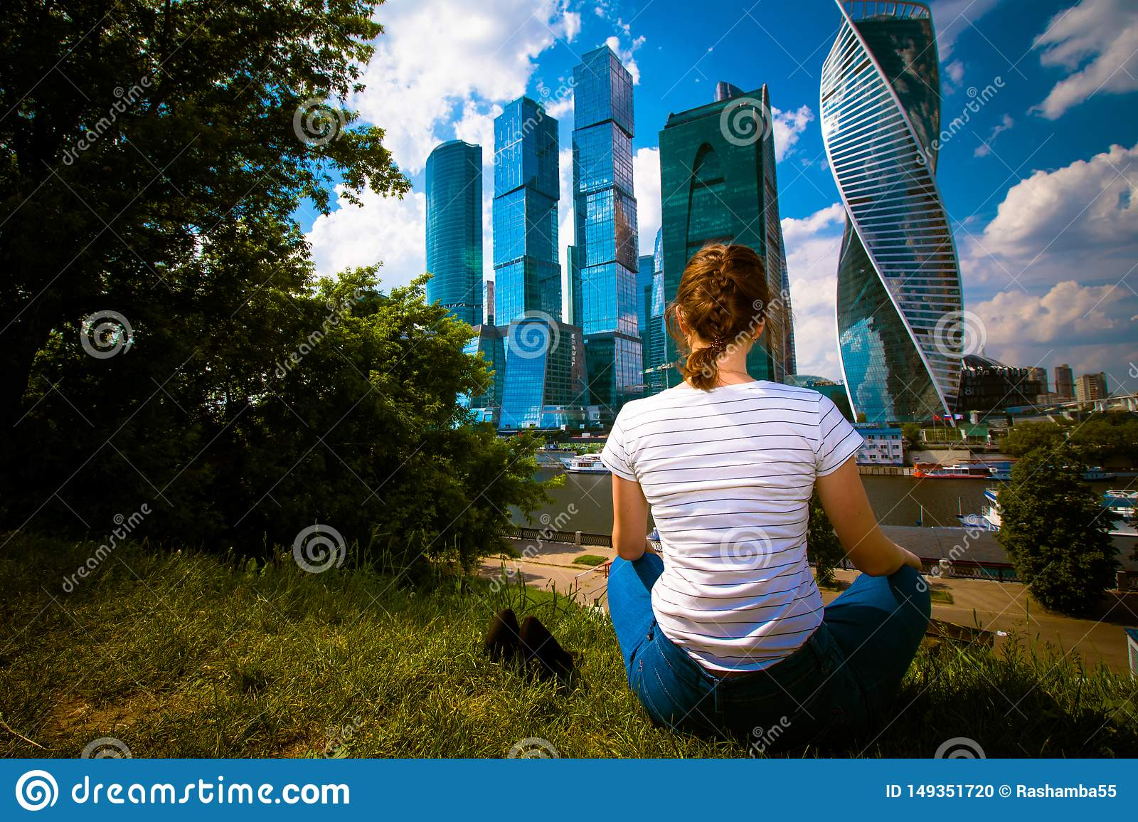 Girl sitting on the grass and relaxing. She is in blue jeans and a white t-shirt. Landscape with skyscrapers