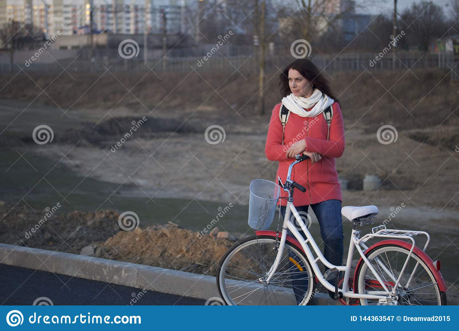 The girl leans on a parked bike. Rest on the spring cycle