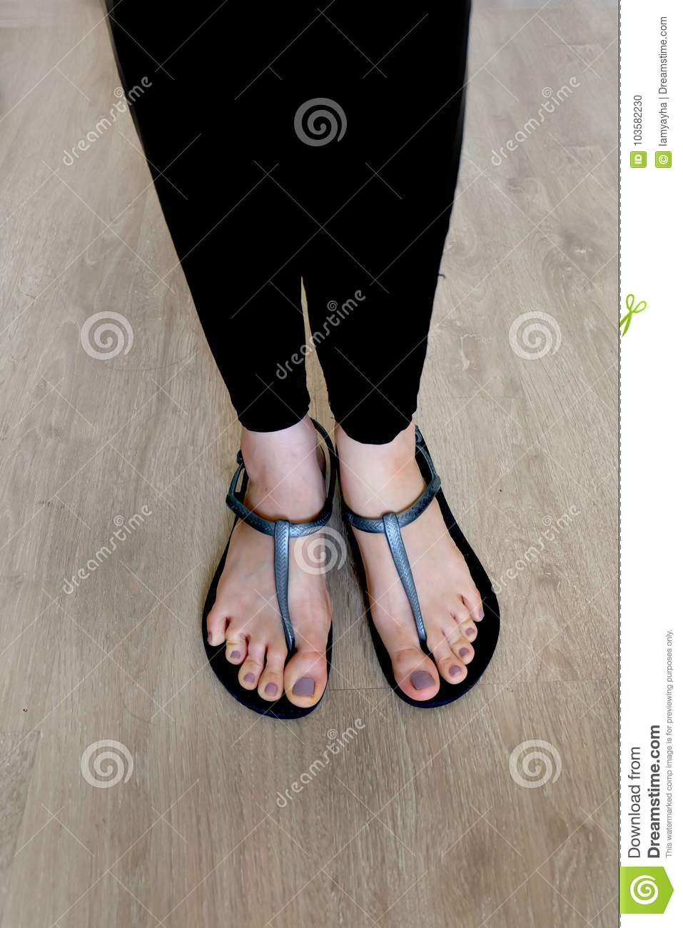 94e10f86f74e3a Girl Legs And Feet Wear Black Sandals On Wooden Background Stock ...