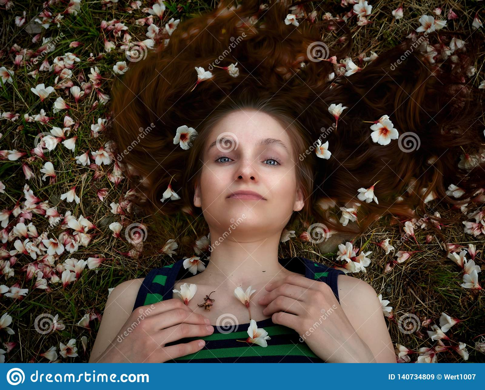 The girl lies on the grass, covered with white flowers