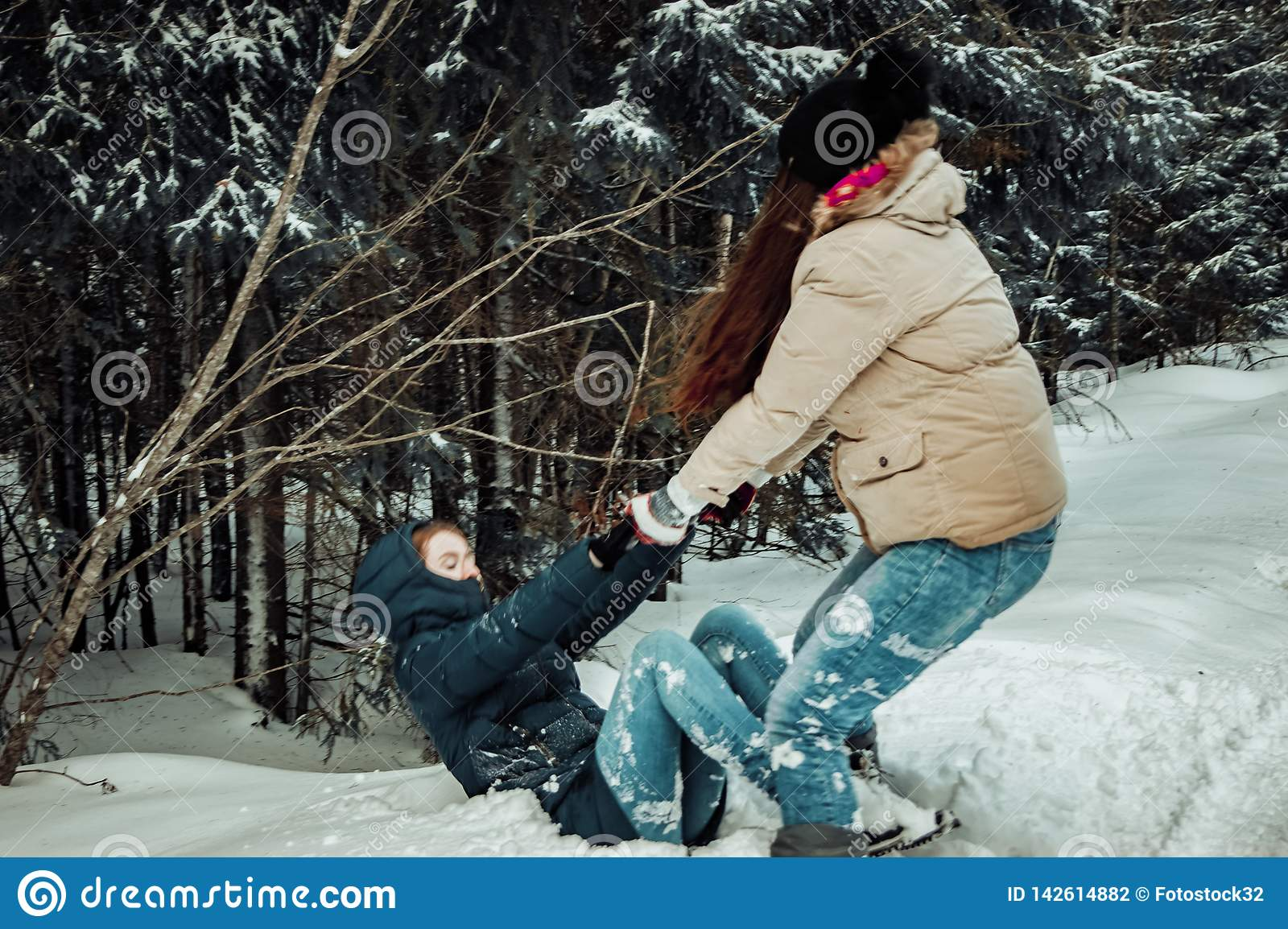 The girl lifts her friend out of the snow