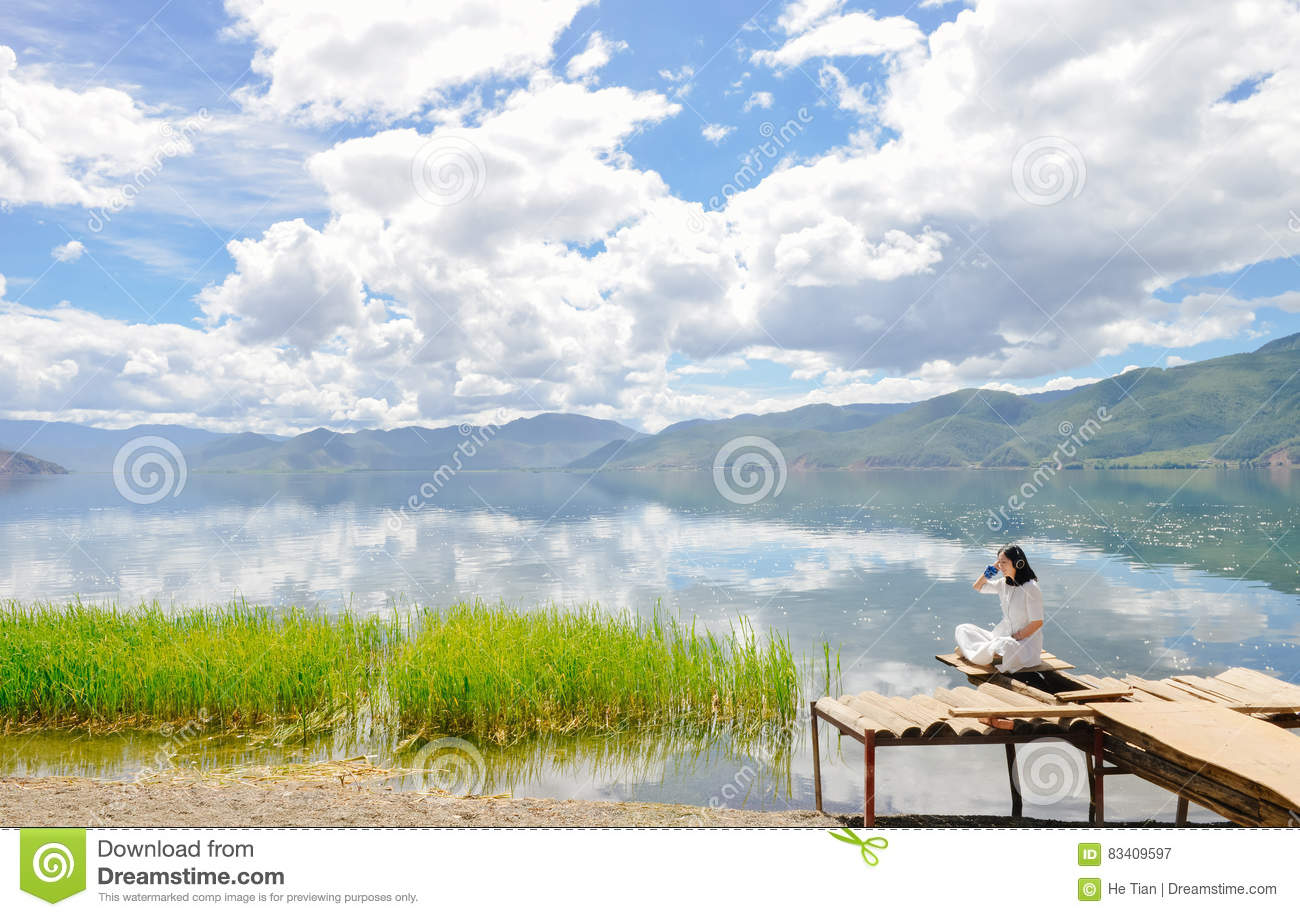 Girl Listen To Music Sitting On Platform On Beach Stock