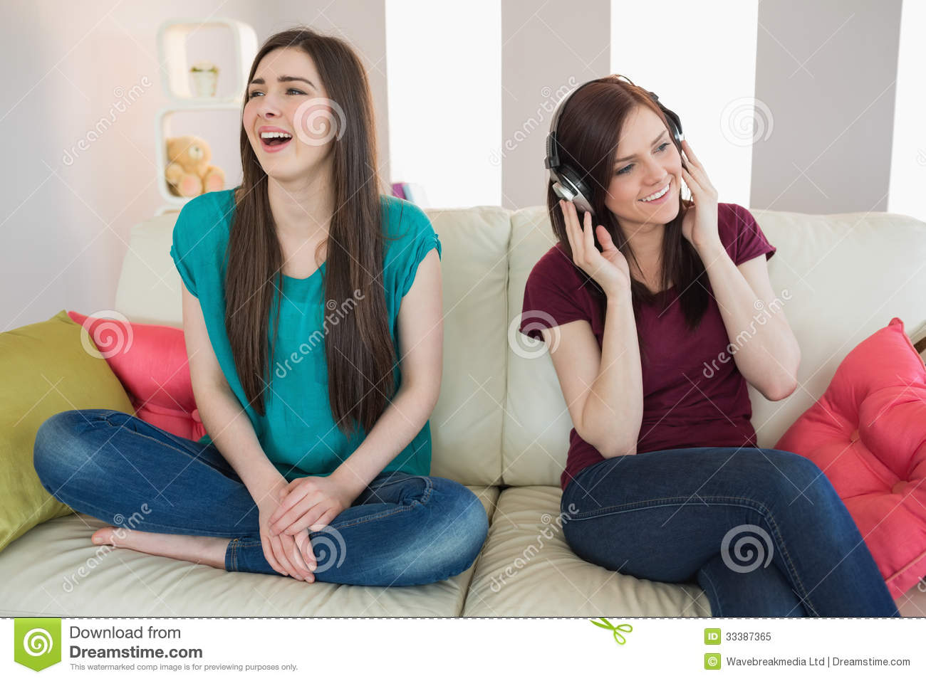 Girl Listening To Music With Her Friend Beside Her On The ...