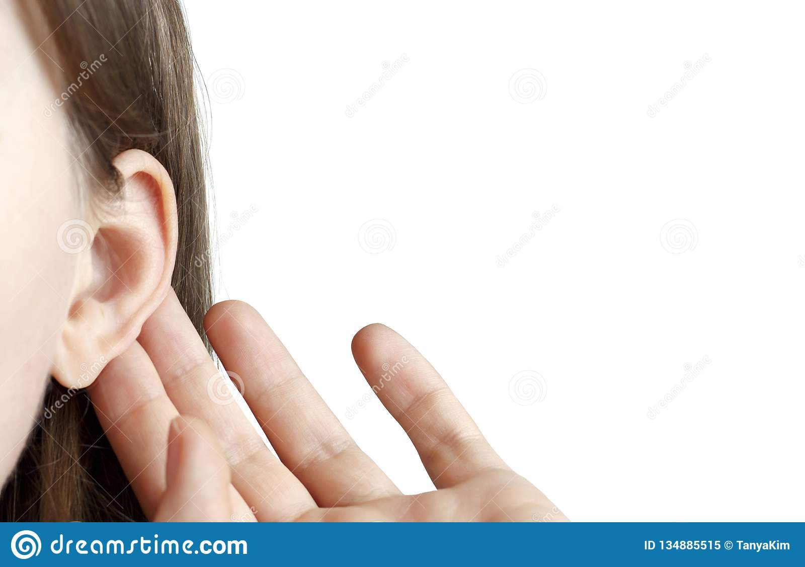 The girl listens attentively with her palm to her ear, close-up isolated on white background, indoors, the news concept