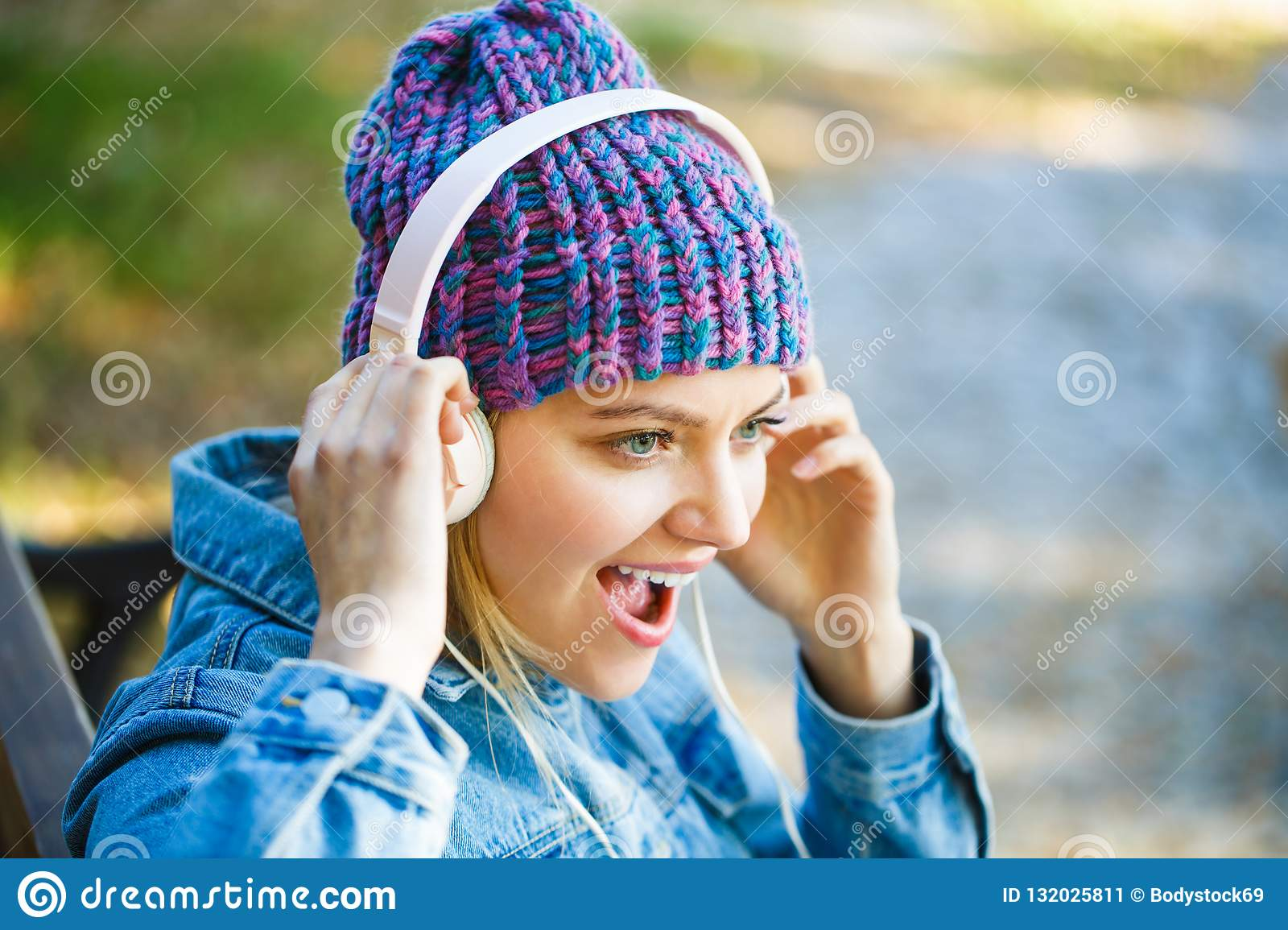 Girl listens to music in headphones. Listening to music.Autumn melody concept. Young woman with big headphones. Cheerful