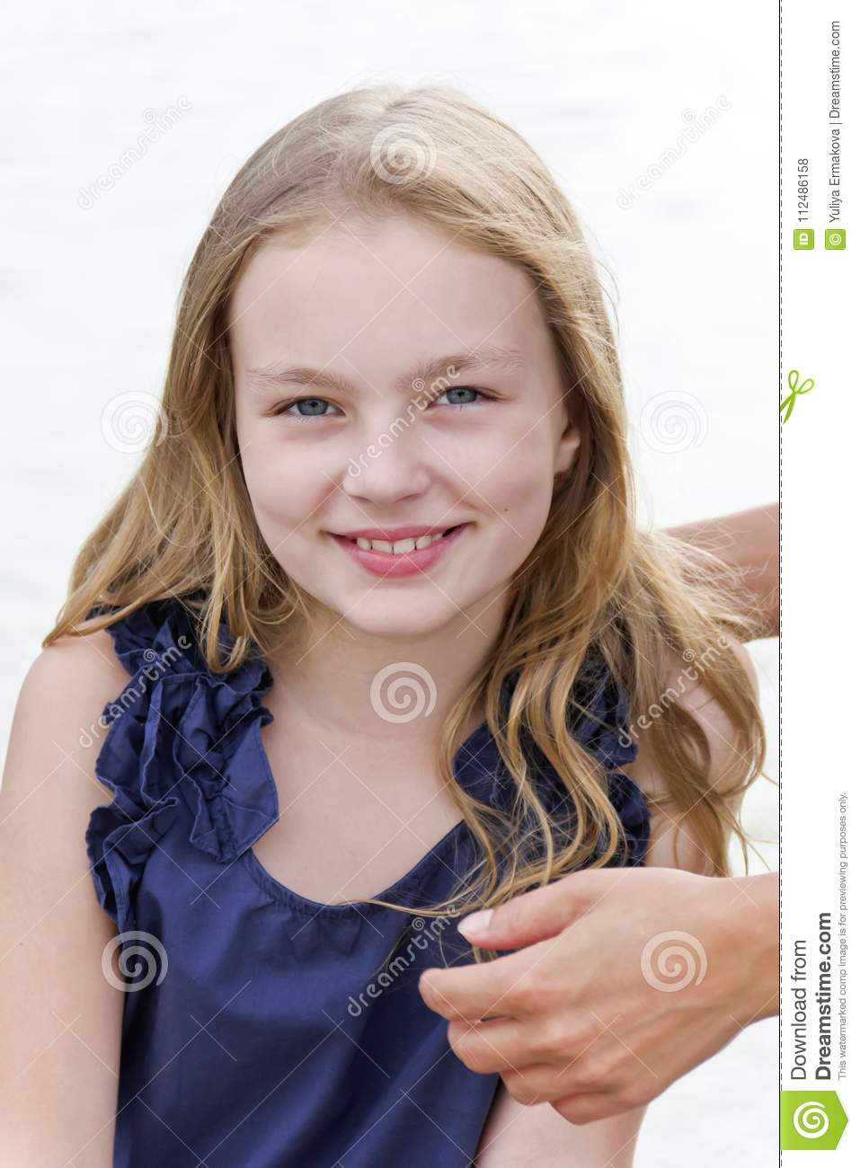 Girl with long blond hair and mother hands