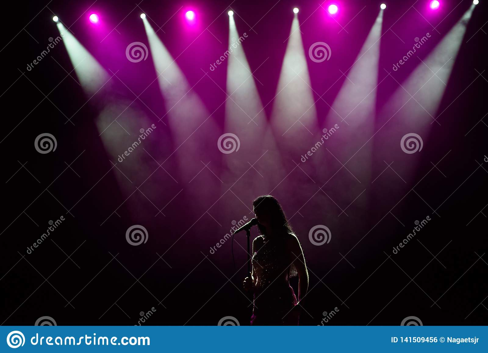 Girl in long gown performing on stage. Girl singing on the stage in front of the lights. Silhouette of singer standing