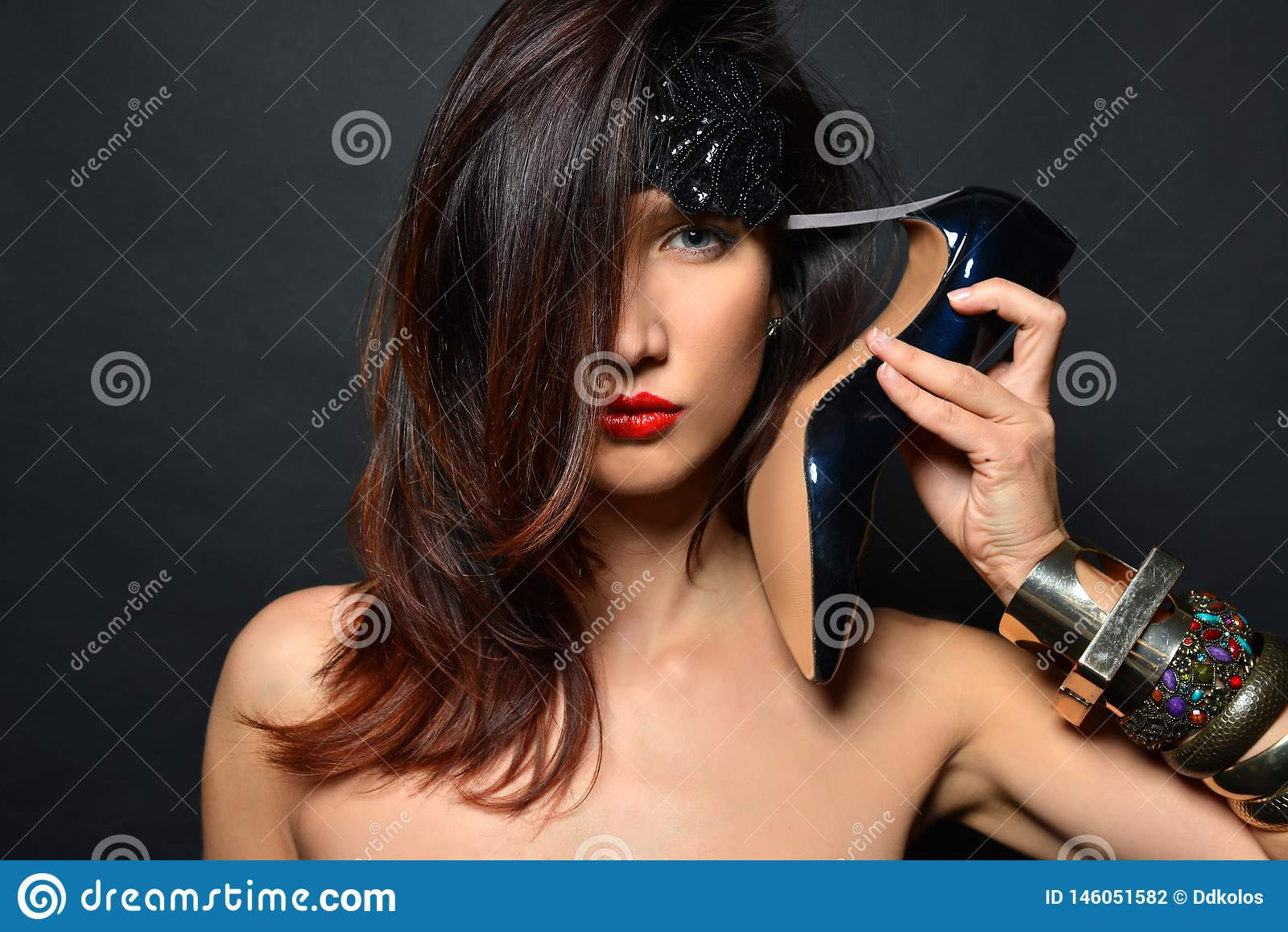 Girl with long hair, red lips and jewelry from bracelets of black high-heeled shoes Put the heel to his temple like a gun