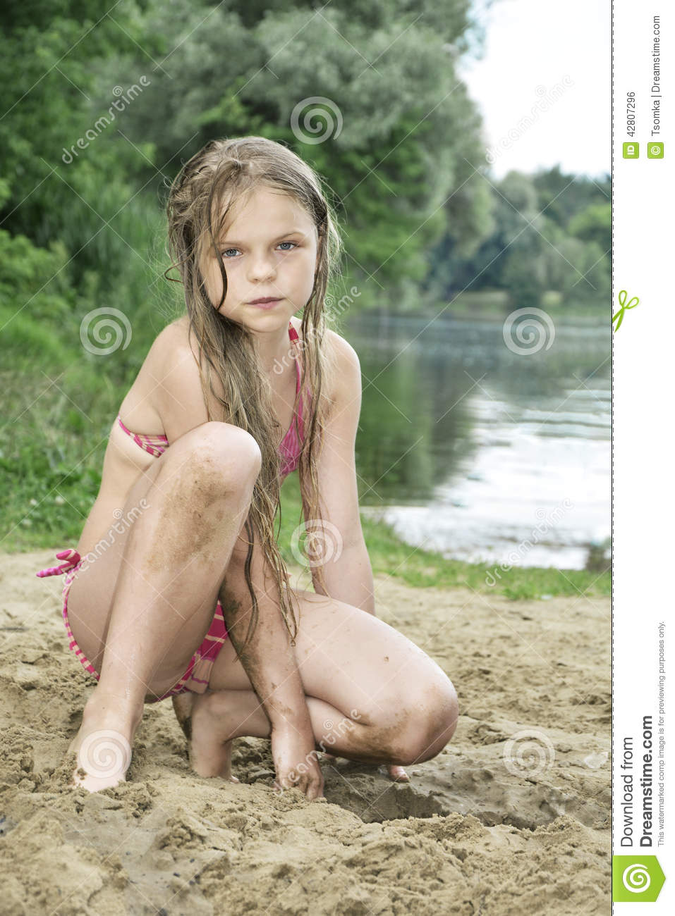 Girl With Long Hair Sitting On The Sand On The Beach Near