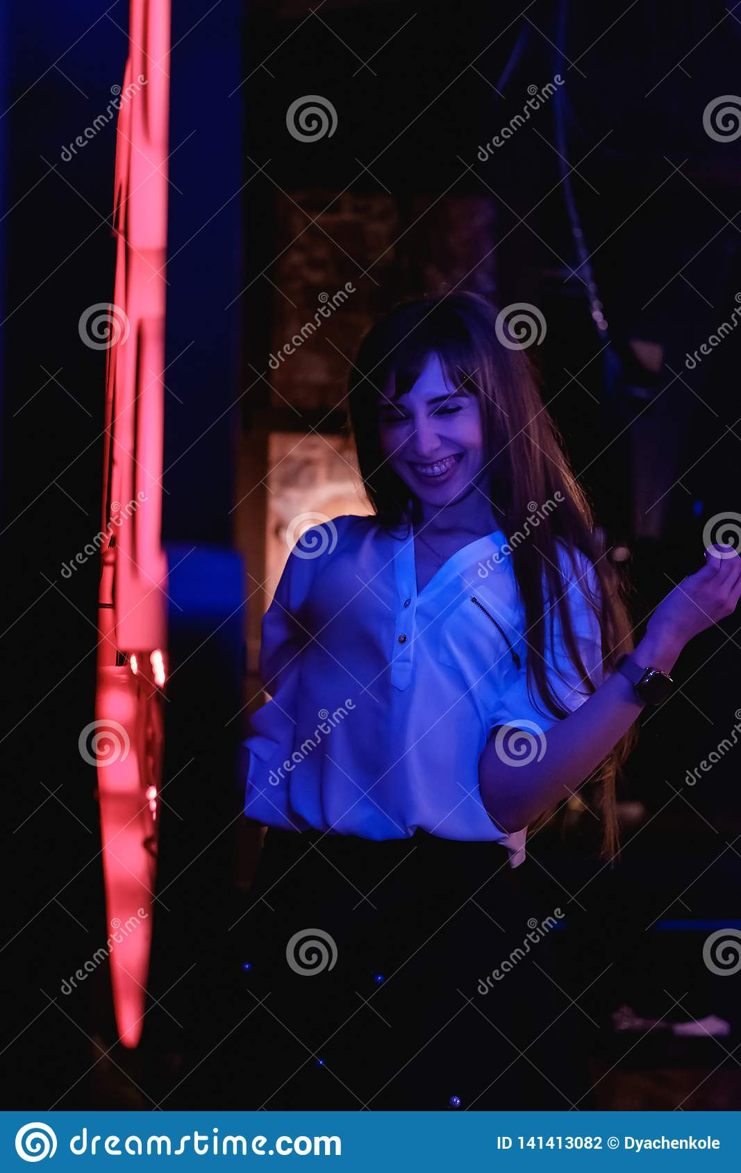 A girl with long hair in a white blouse is dancing and laughing in a club near a bright LED sign