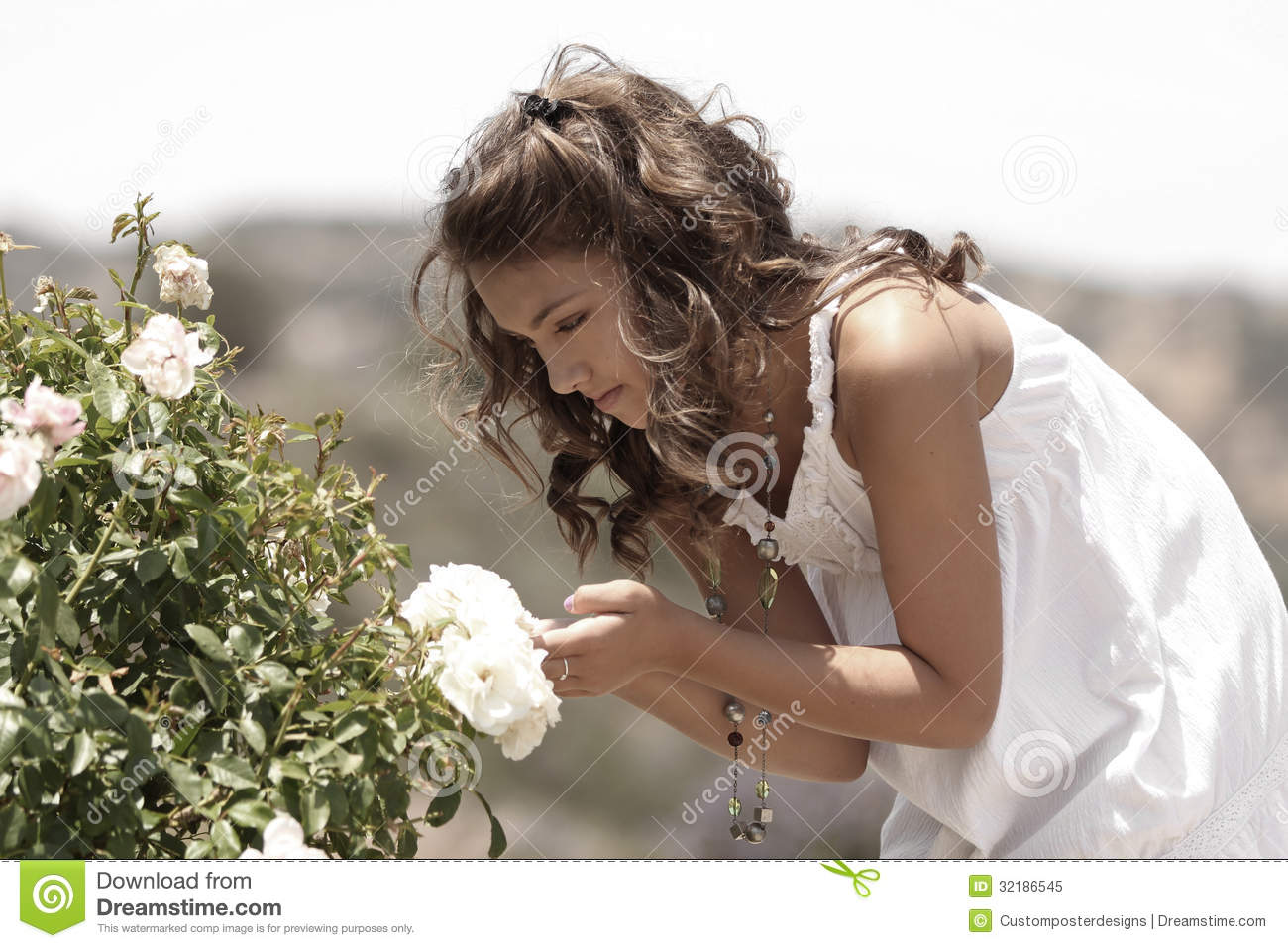 A girl looking at a flower.