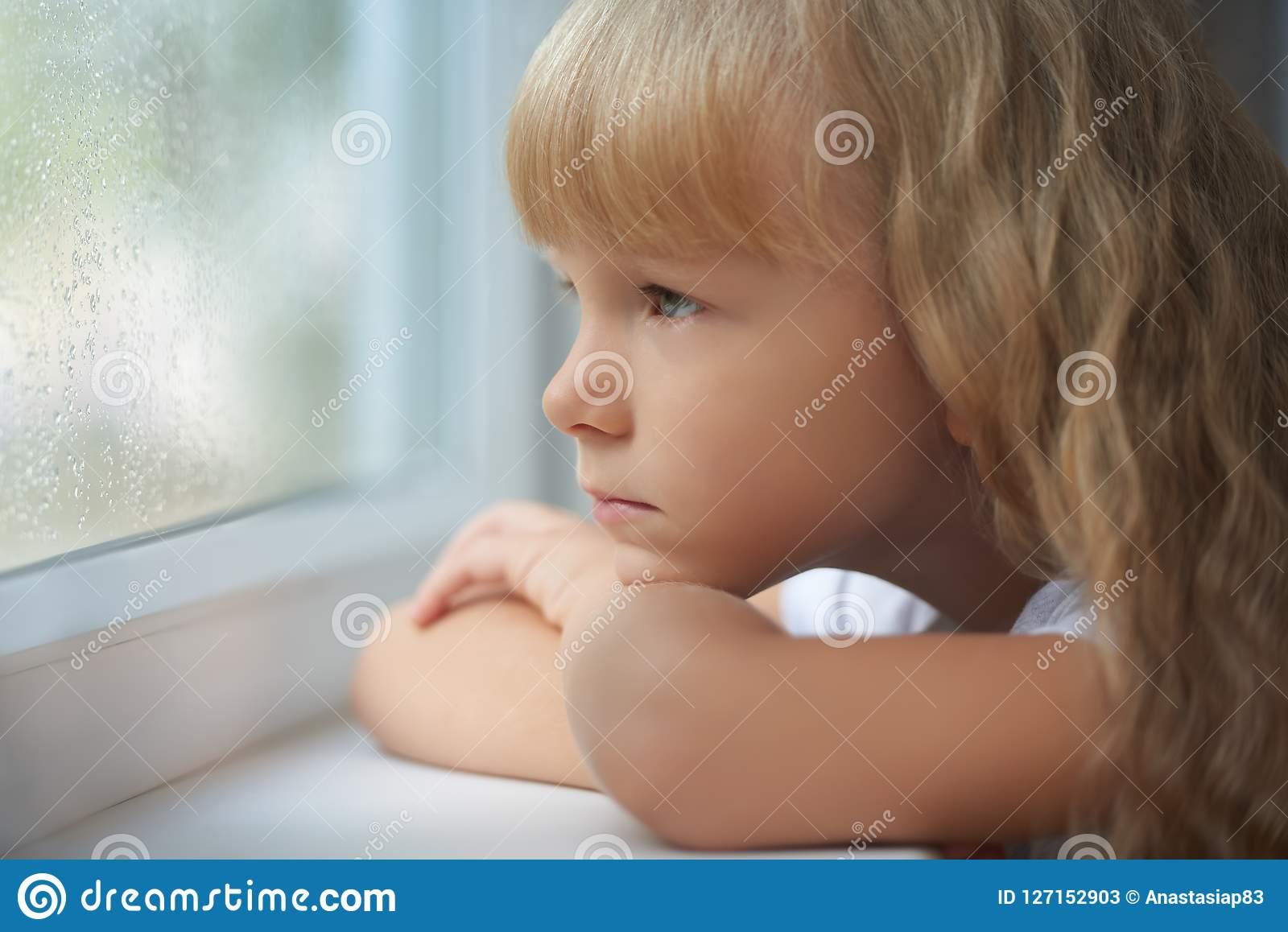 A girl looking out of the window on a rainy day