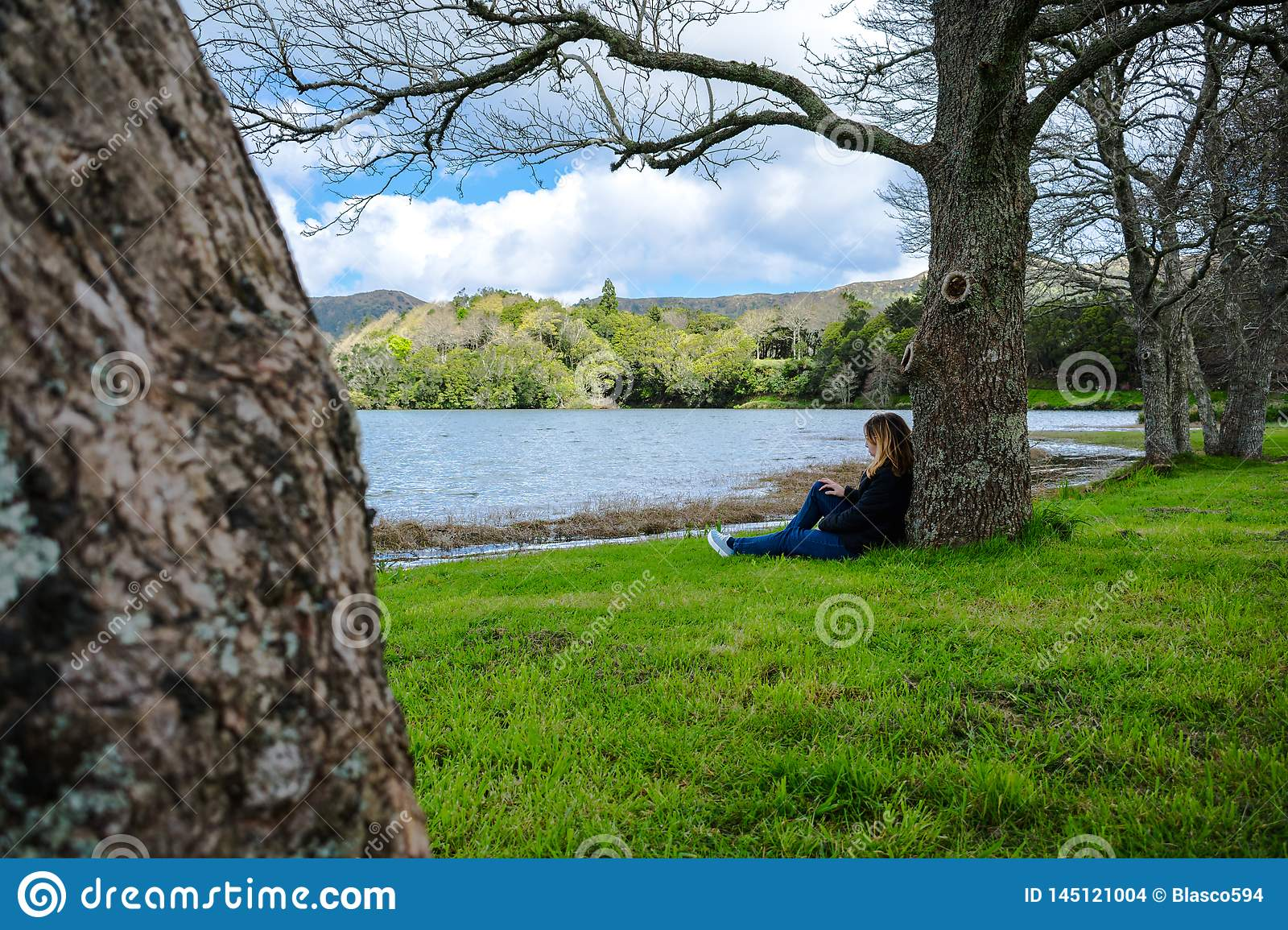 Girl looking over Sete Cidades lake into the mountains, Azores, Portugal