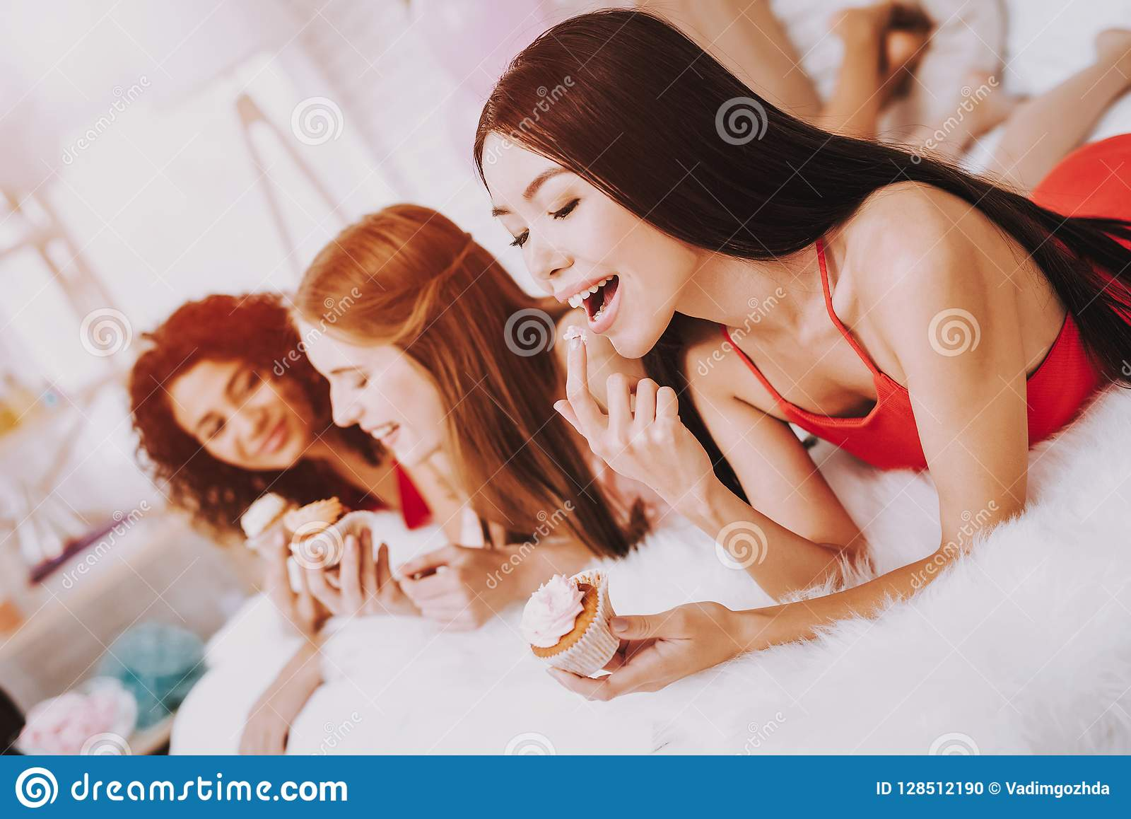 Women in Red Dresses Lying on Bed Eating Cupcakes.