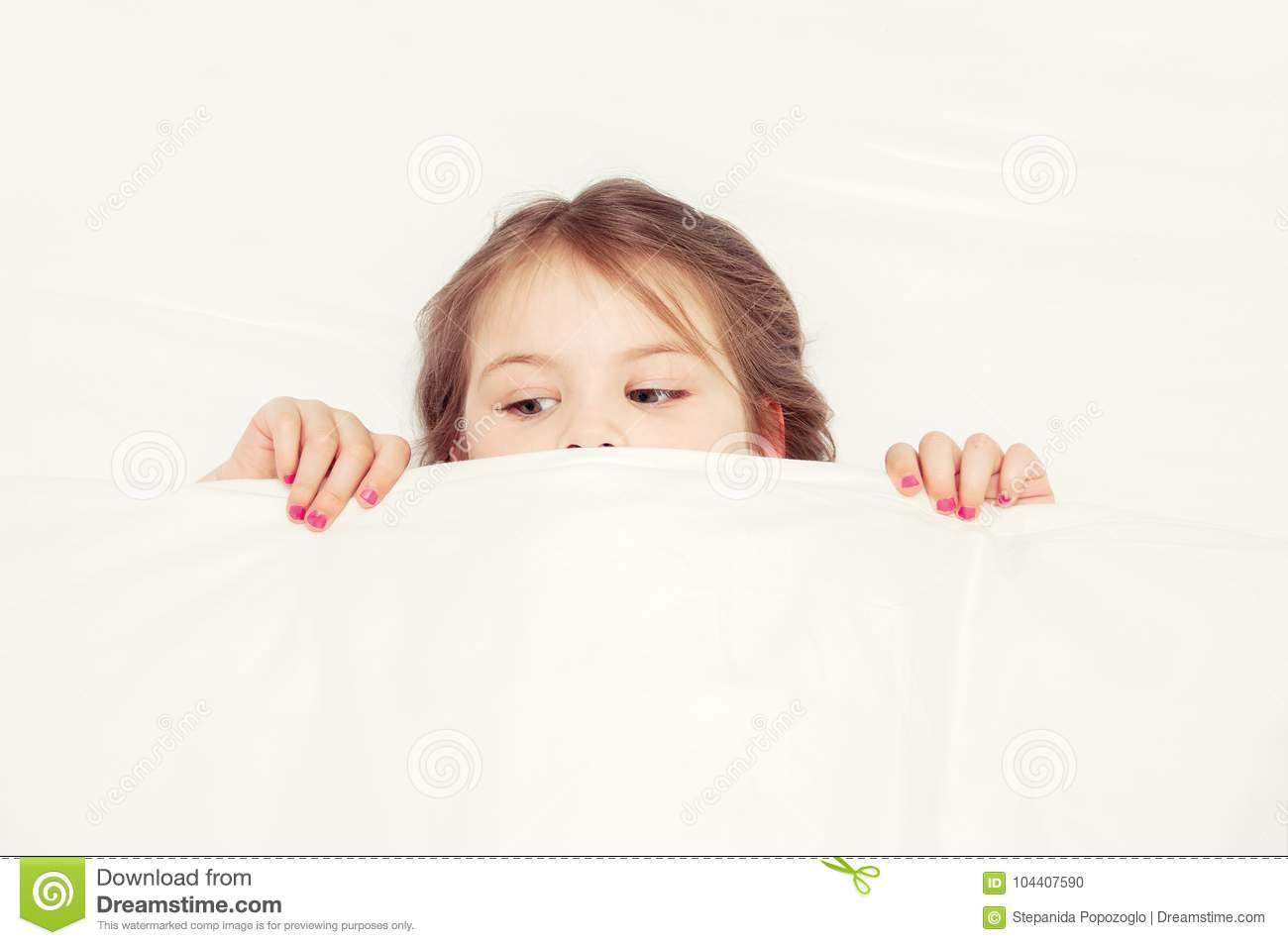The girl is lying on the couch in the bedroom and covered herself with a blanket for fear. Little girl having childhood nightmare