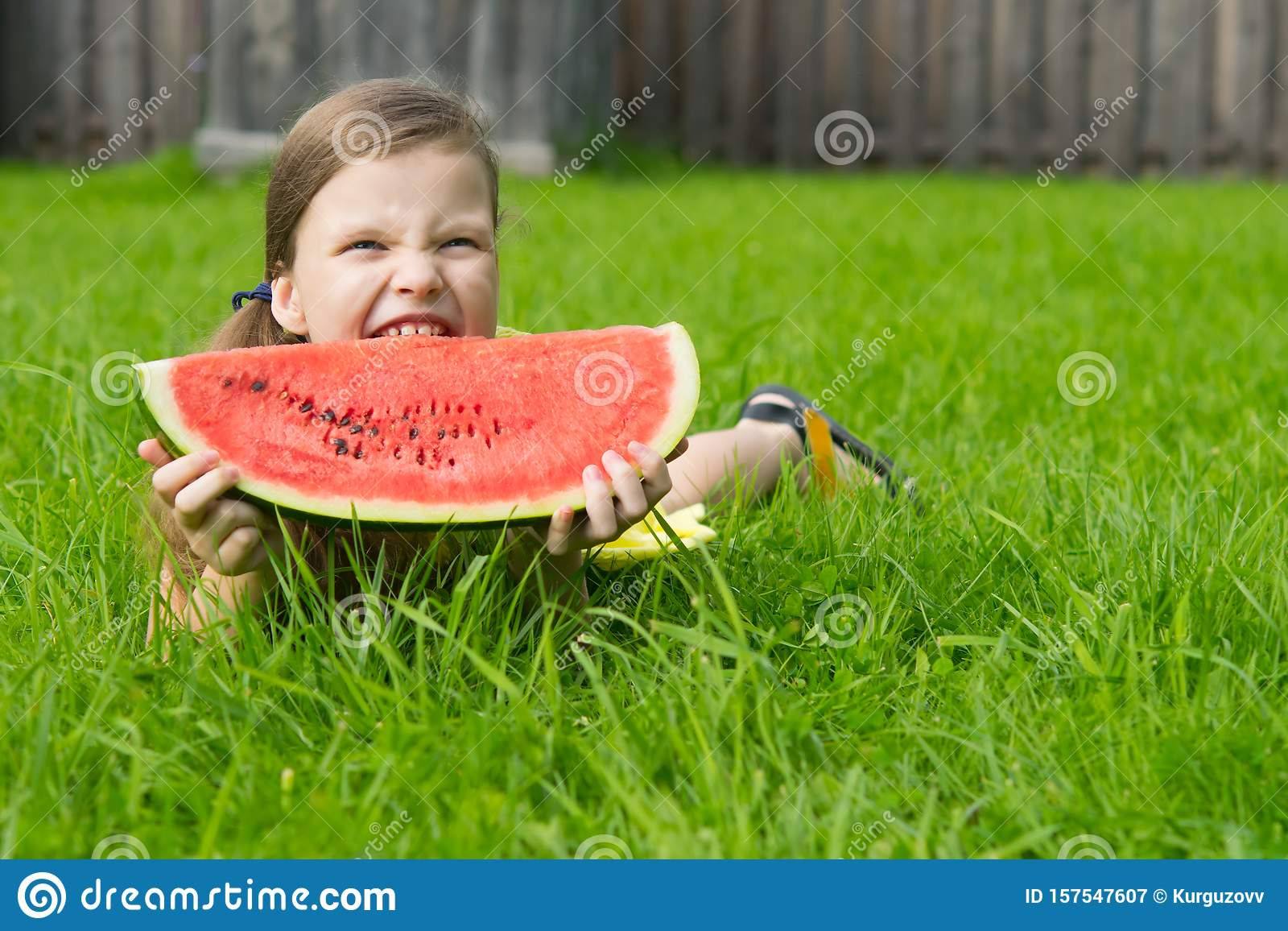 Girl lying on the lawn. and holding a large slice of watermelon on a green background