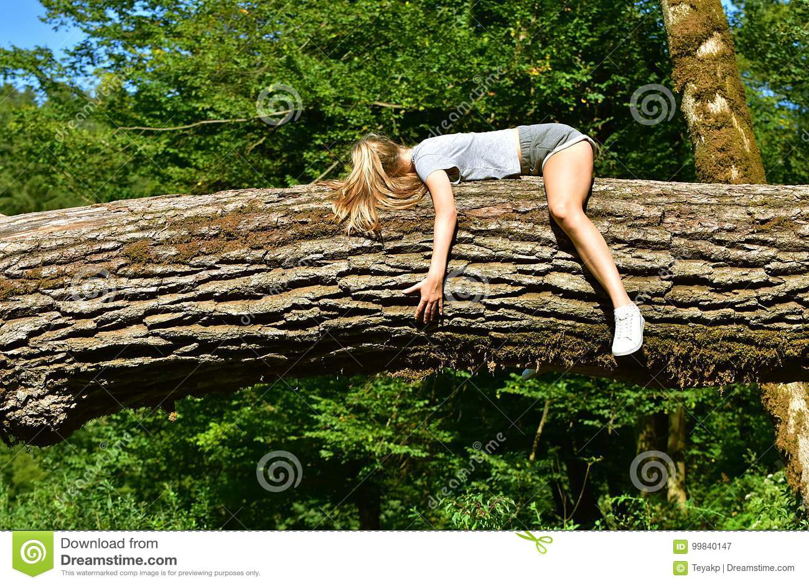 Girl lying on tree trunk