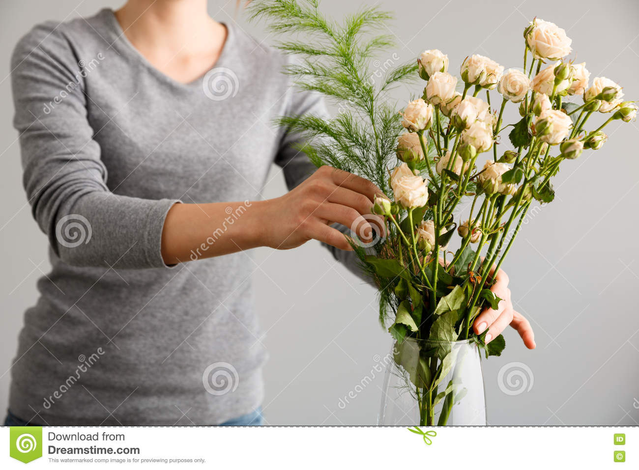 Girl make bouquet over gray background putting flowers in vase. & Girl Make Bouquet Over Gray Background Putting Flowers In Vase ...