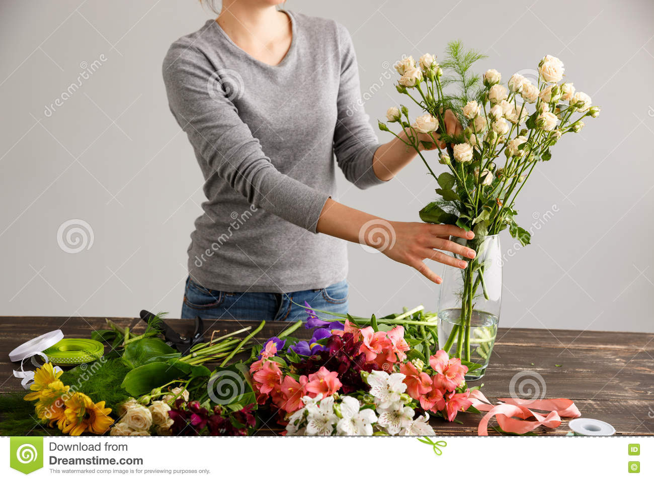 Girl in gray blouse and jeans make a bouquet over gray background putting roses in vase flowers and vase on wood table. & Girl Make Bouquet Over Gray Background Putting Flowers In Vase ...