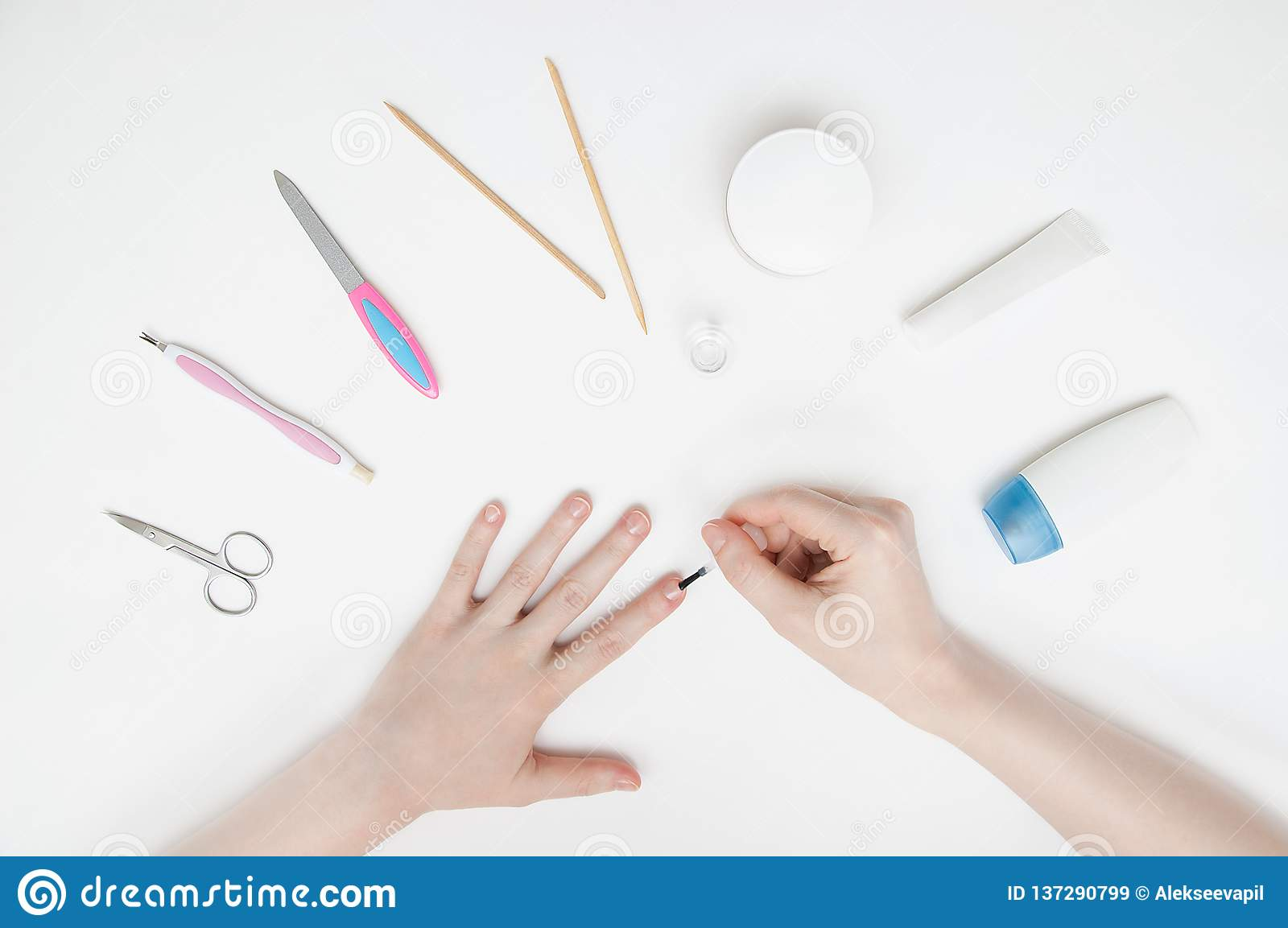 girl makes herself a manicure on a white table. Close-up