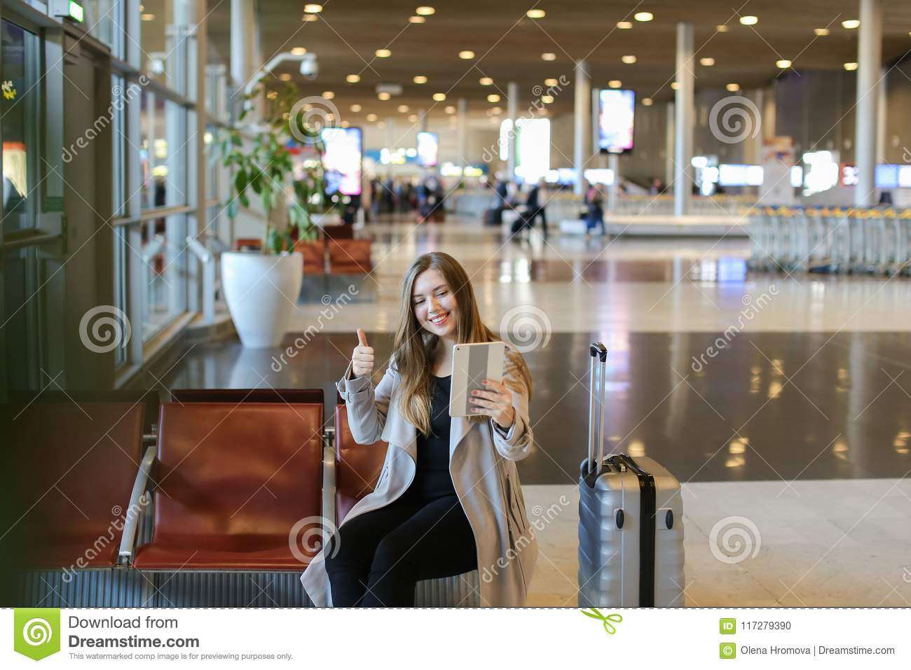 Girl Making Video Call By Tablet In Airport Hall And Sitting Near