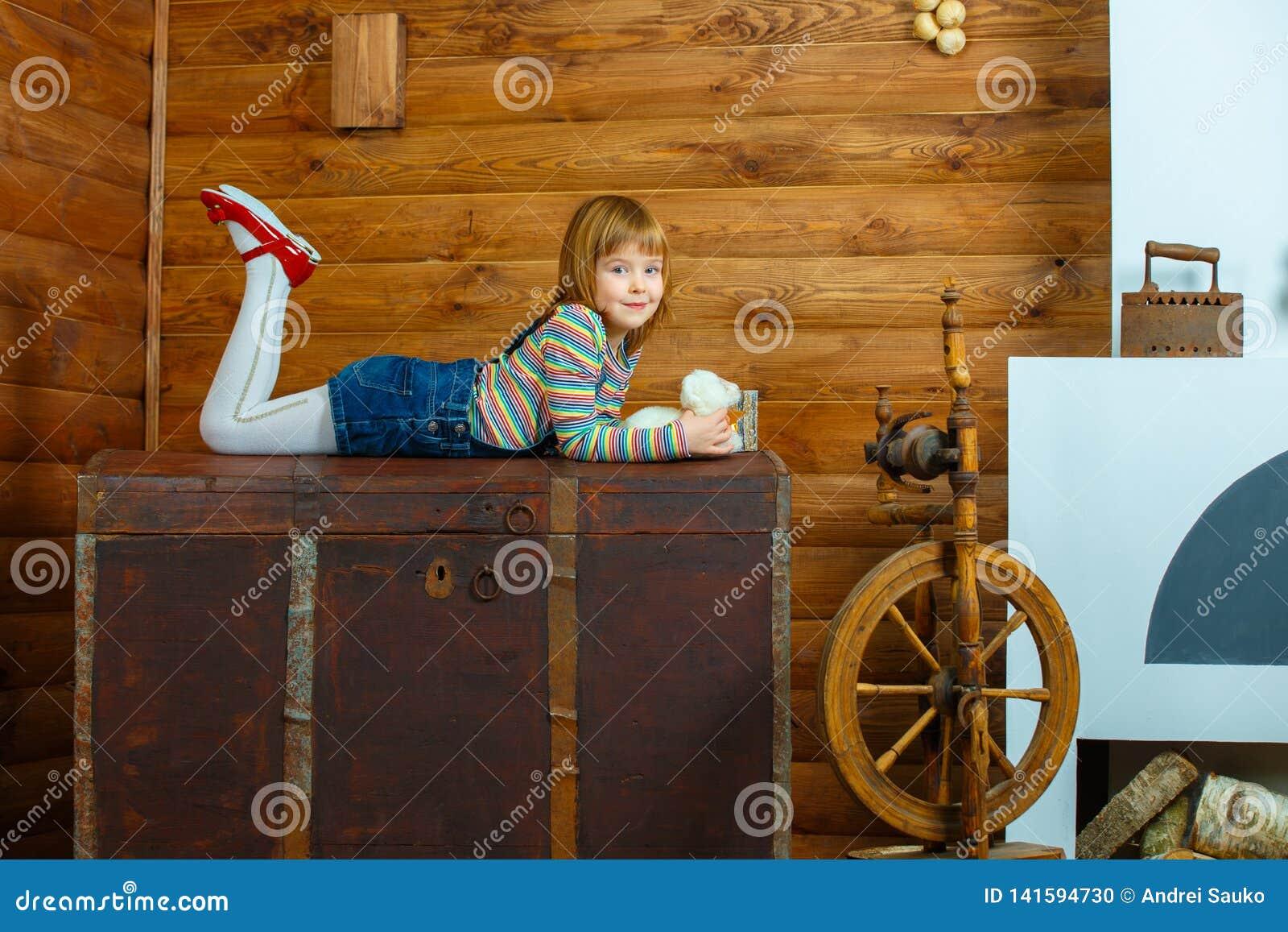Girl Masha is lying on the old chest