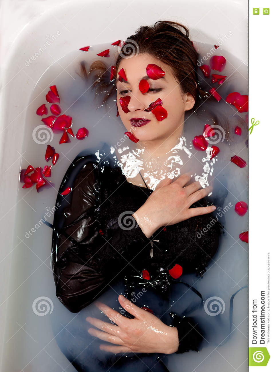 e4e37dc18ee Girl with a black dress enjoying a white milk bath with red rose leaves in  the water and on her face