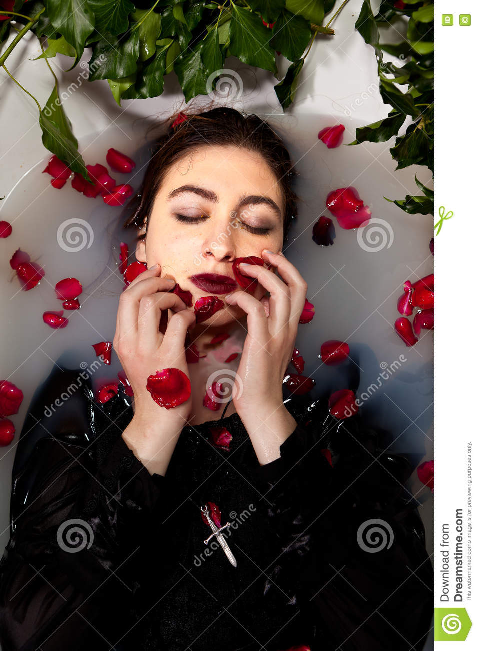 7bdd2e01571 Girl with a black dress enjoying a white milk bath with red leaves of red  roses and ivy