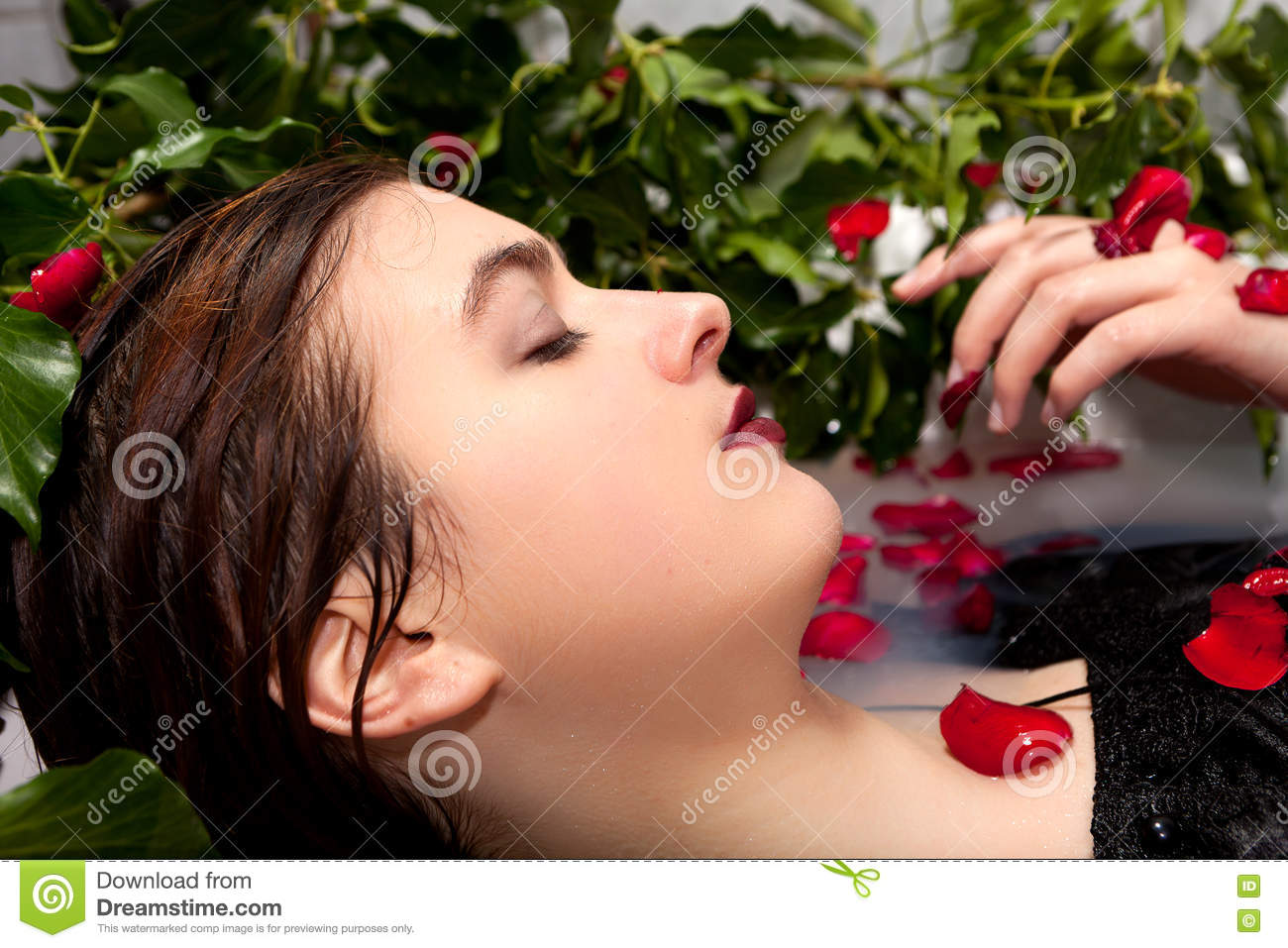 3434f70c3a8 Girl with a black dress enjoying a white milk bath with red rose leaves and  ivy