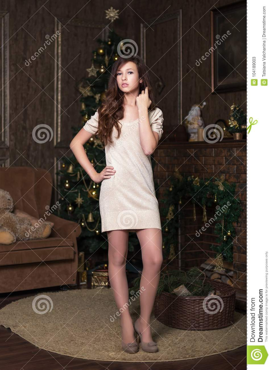 Girl model shows poses on photo shoot in studio with christmas tree